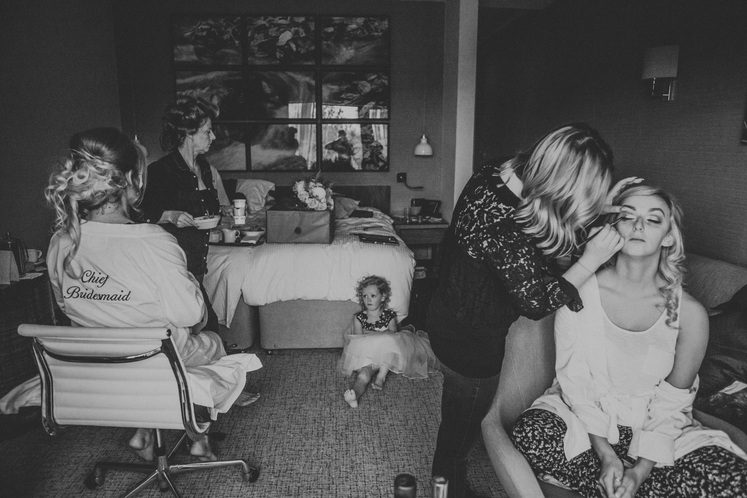 Bride getting her make up done, as others get ready and flower girl sits on the floor.
