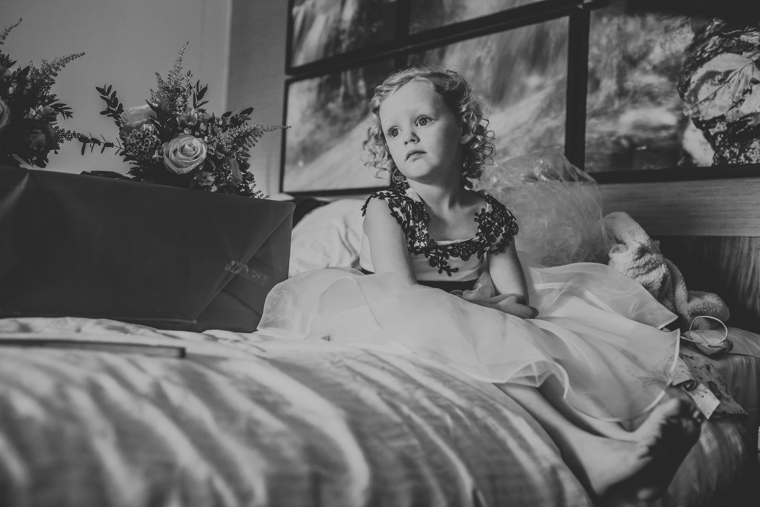 Flower girl sitting on the bed, photograph in black and white.