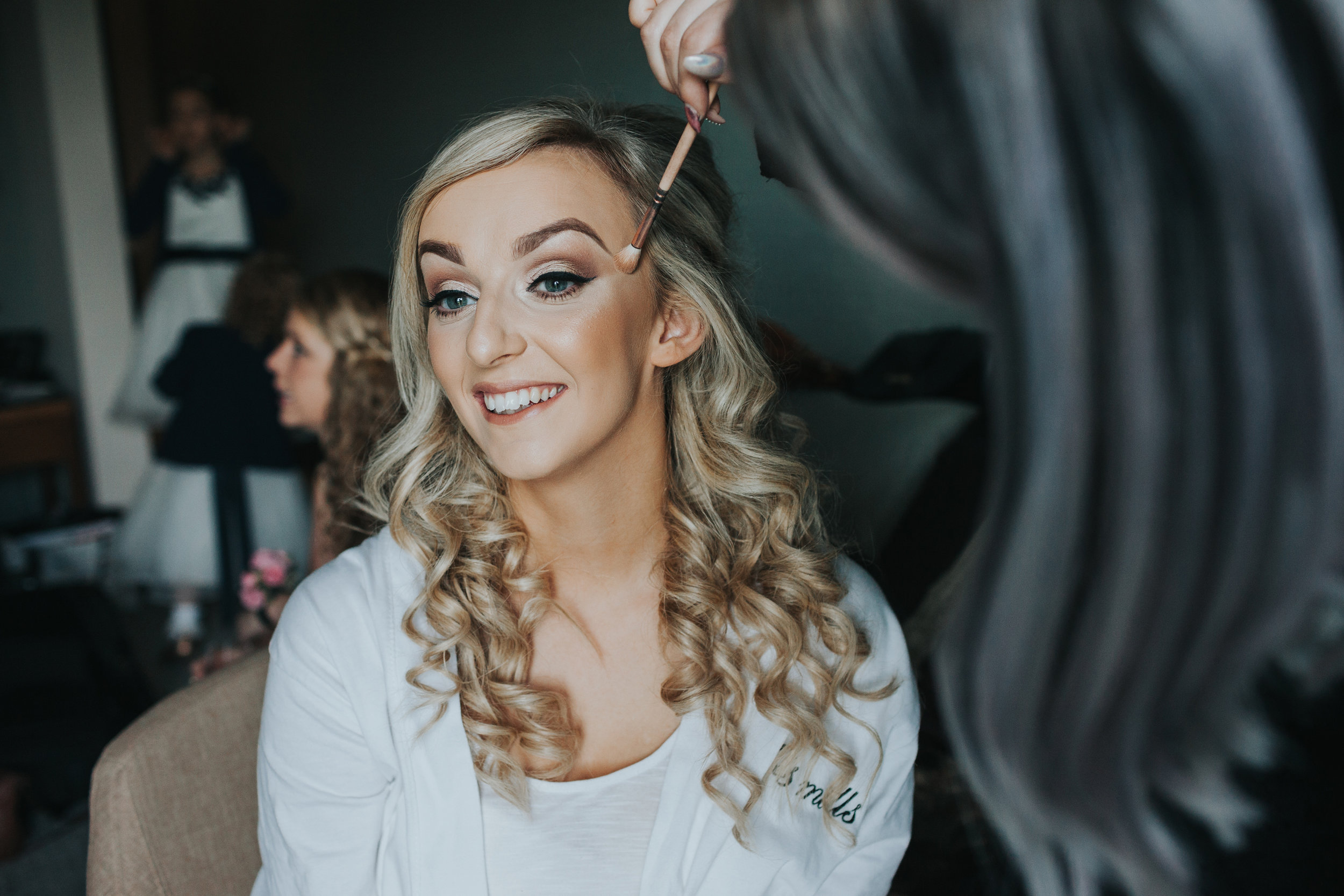 Bride getting her make up put on.
