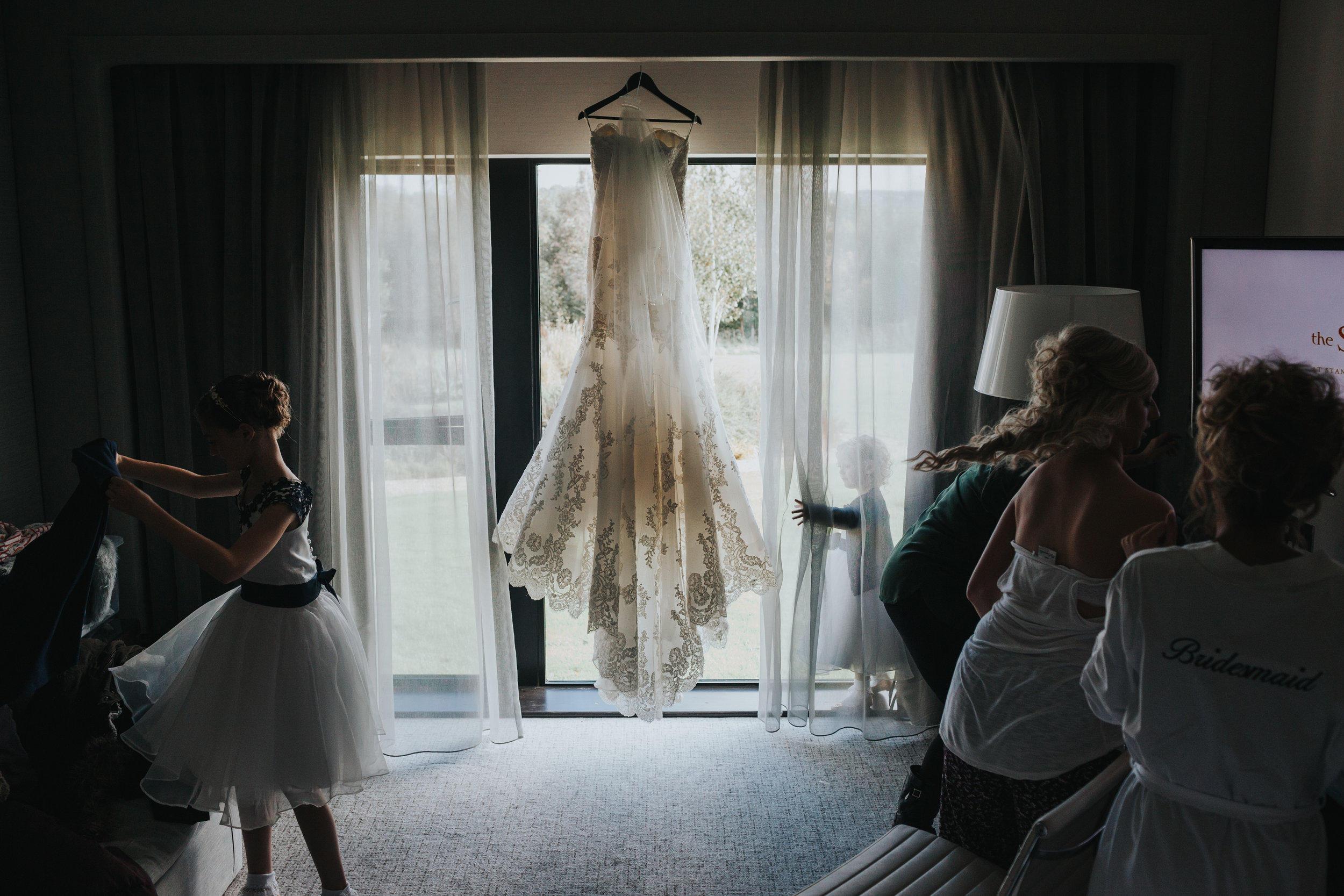 Dress hangs in back ground as bridal party continue to get ready in the shadows.