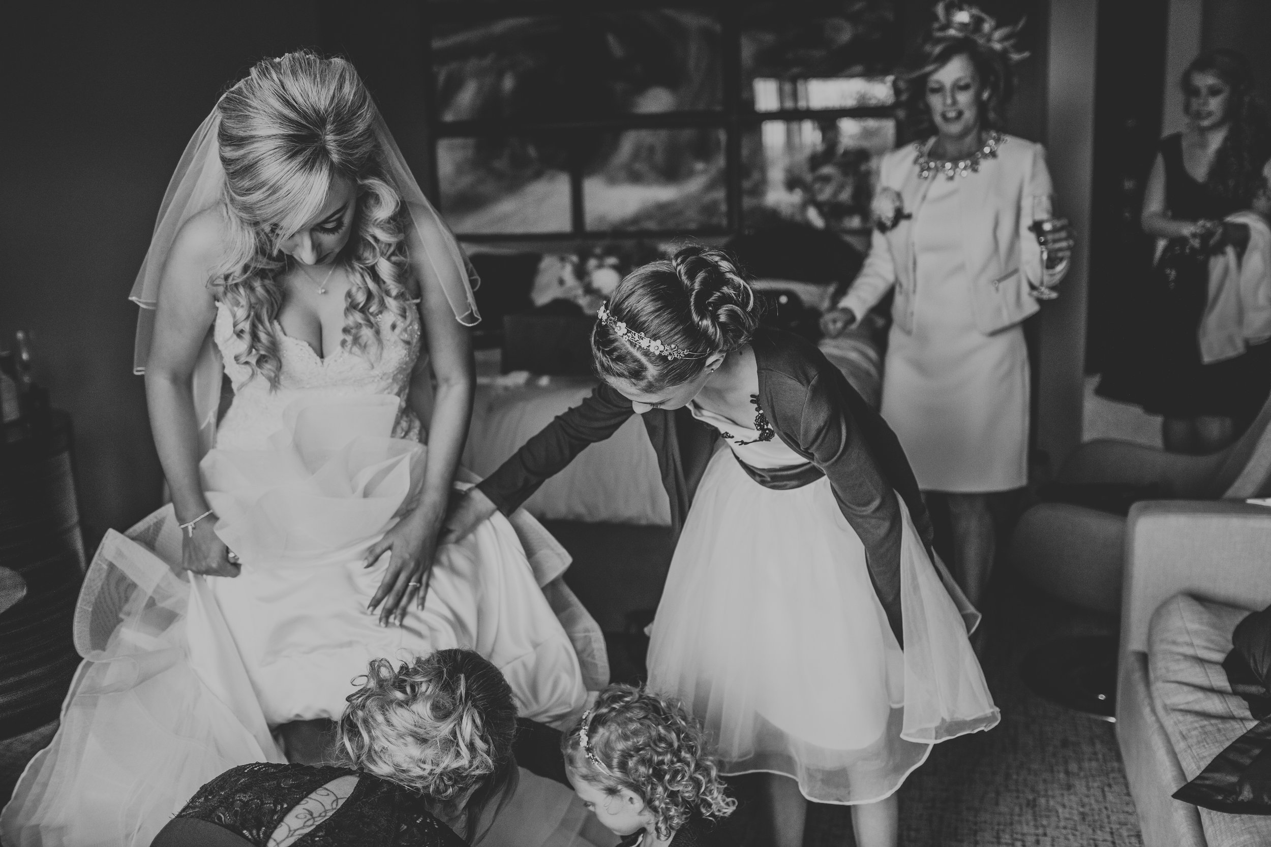 Bride getting ready with her flower girls helping her.