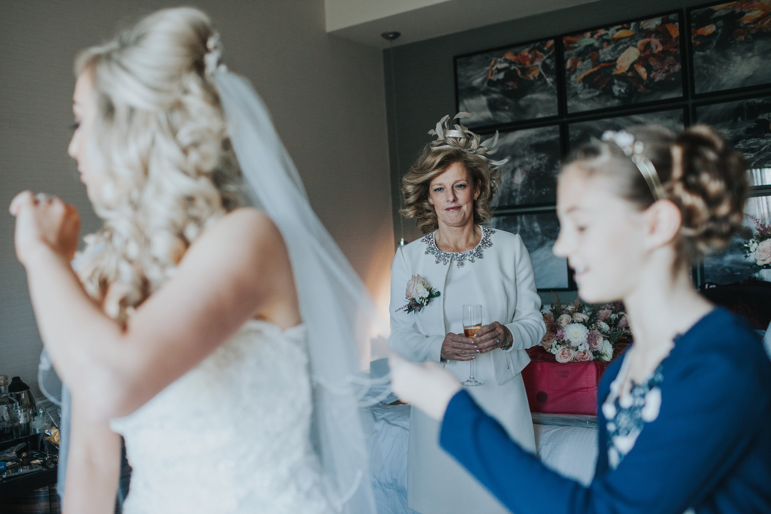 Mother of the Bride looks proudly as her daughter puts on her wedding dress.