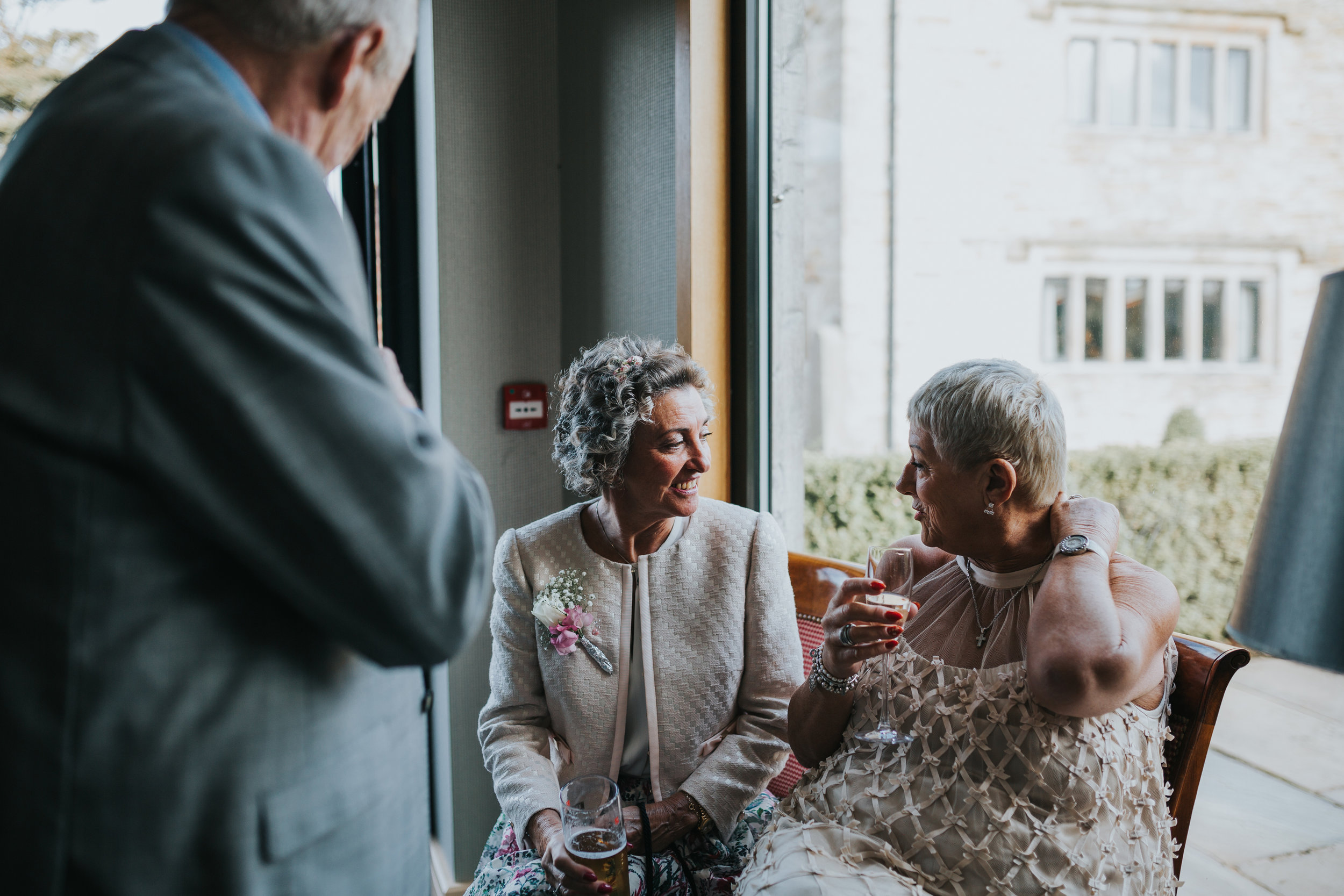 Wedding guests enjoy each others company next to a window.