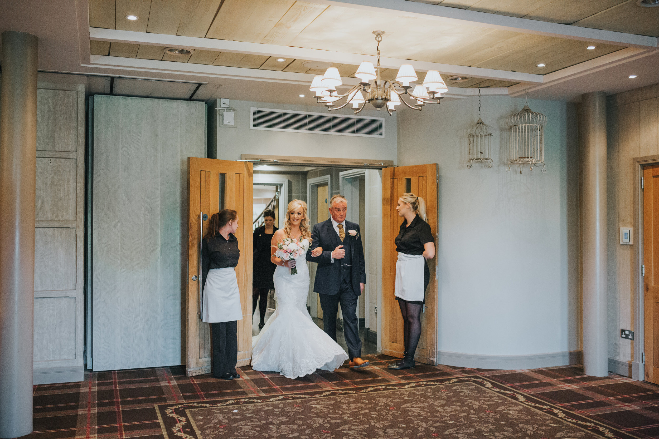 Bride and the father of the bride enter the ceremony room.