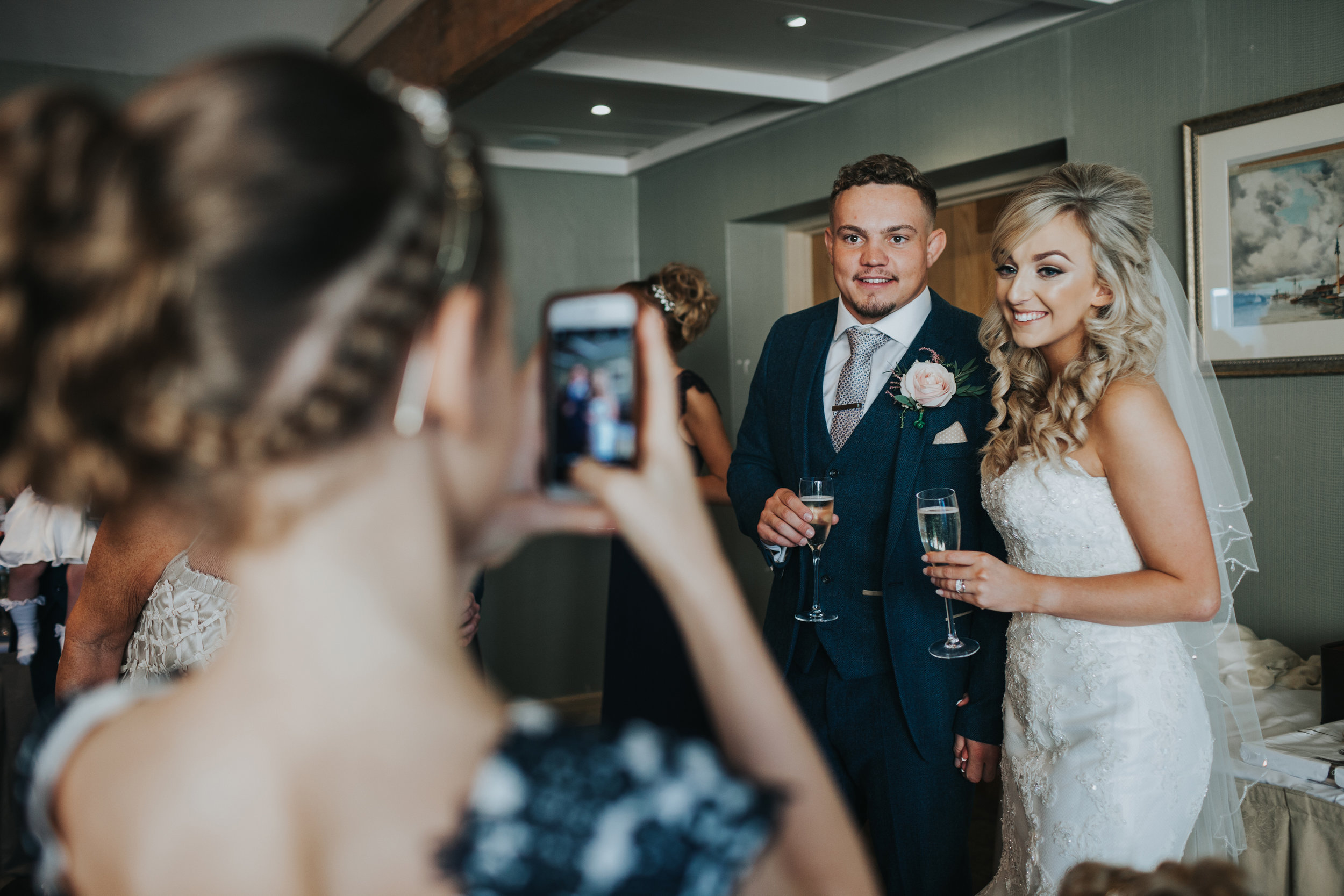 Bride and groom pose for their flower girl to take a photograph on her phone.