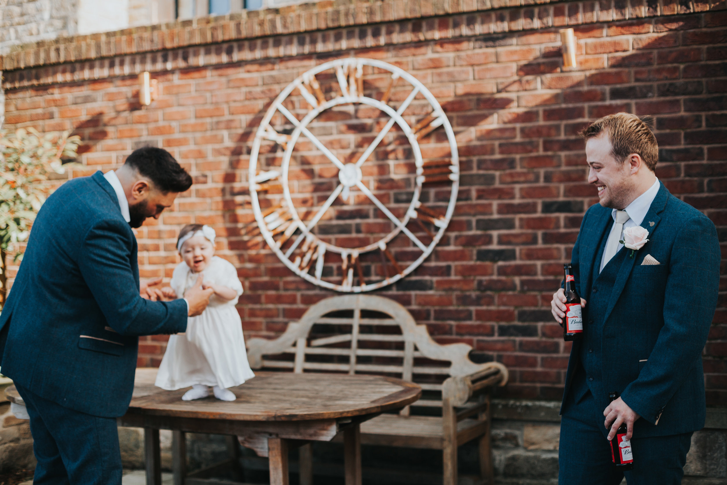 Little girl plays with the groomsmen.
