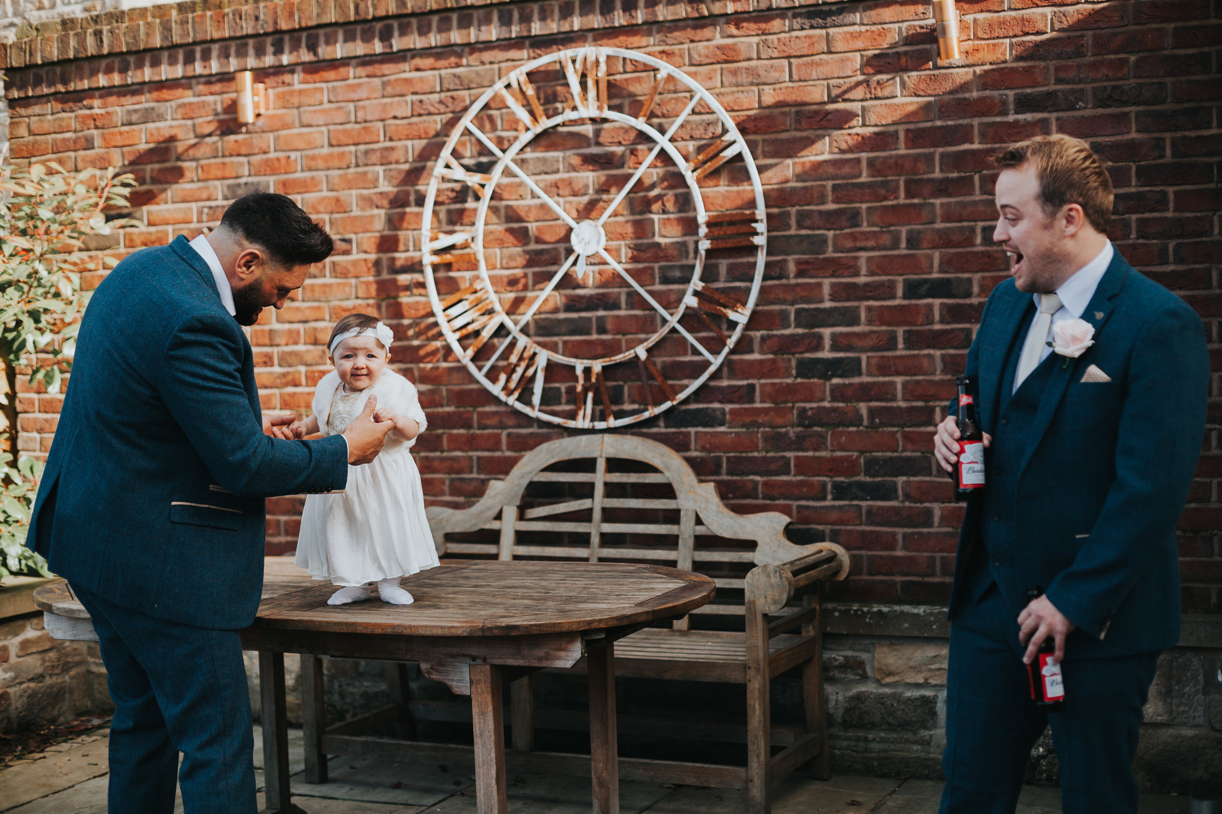 Little girl laughs with groomsmen.