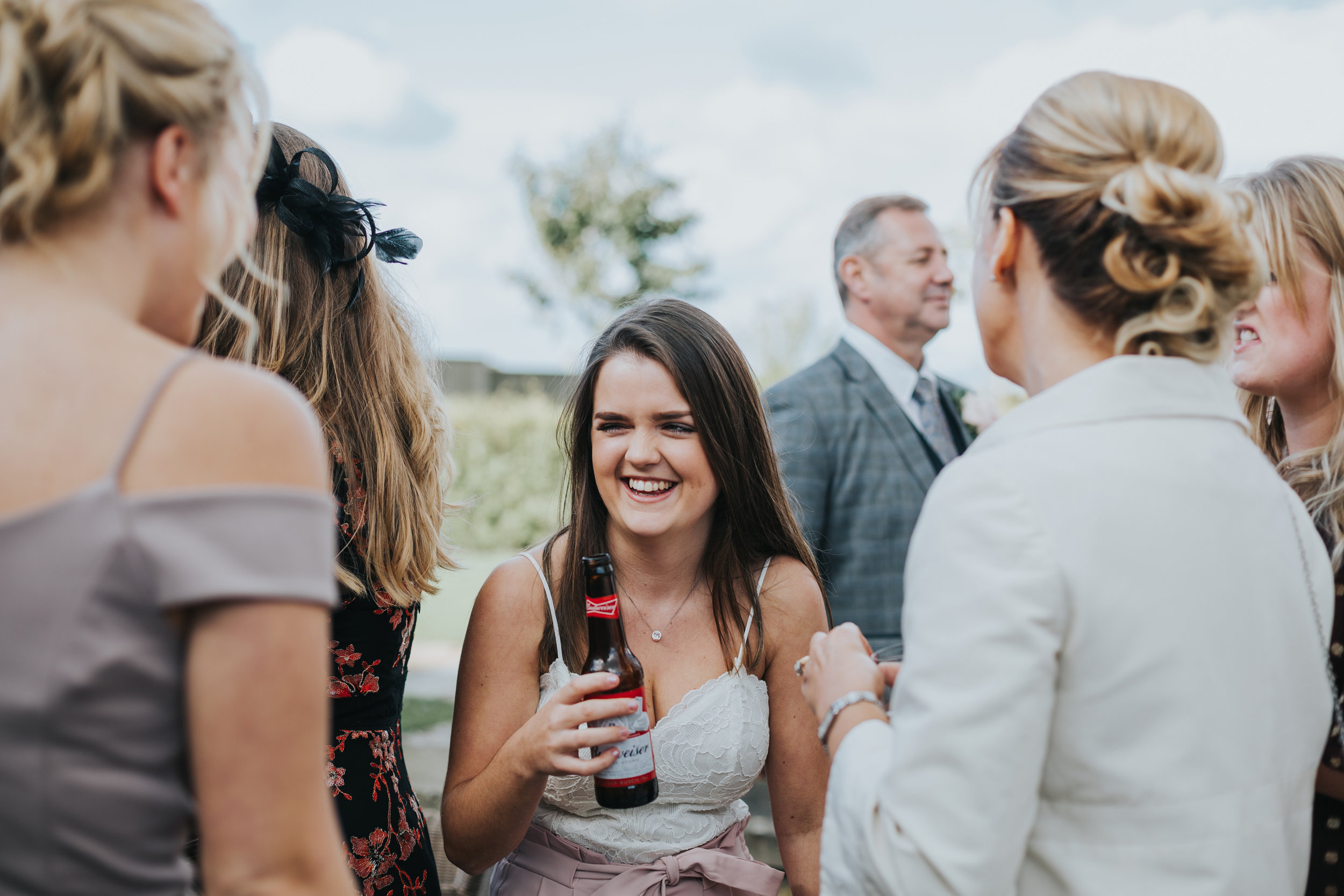 Girl has a beer with her mates at a wedding.