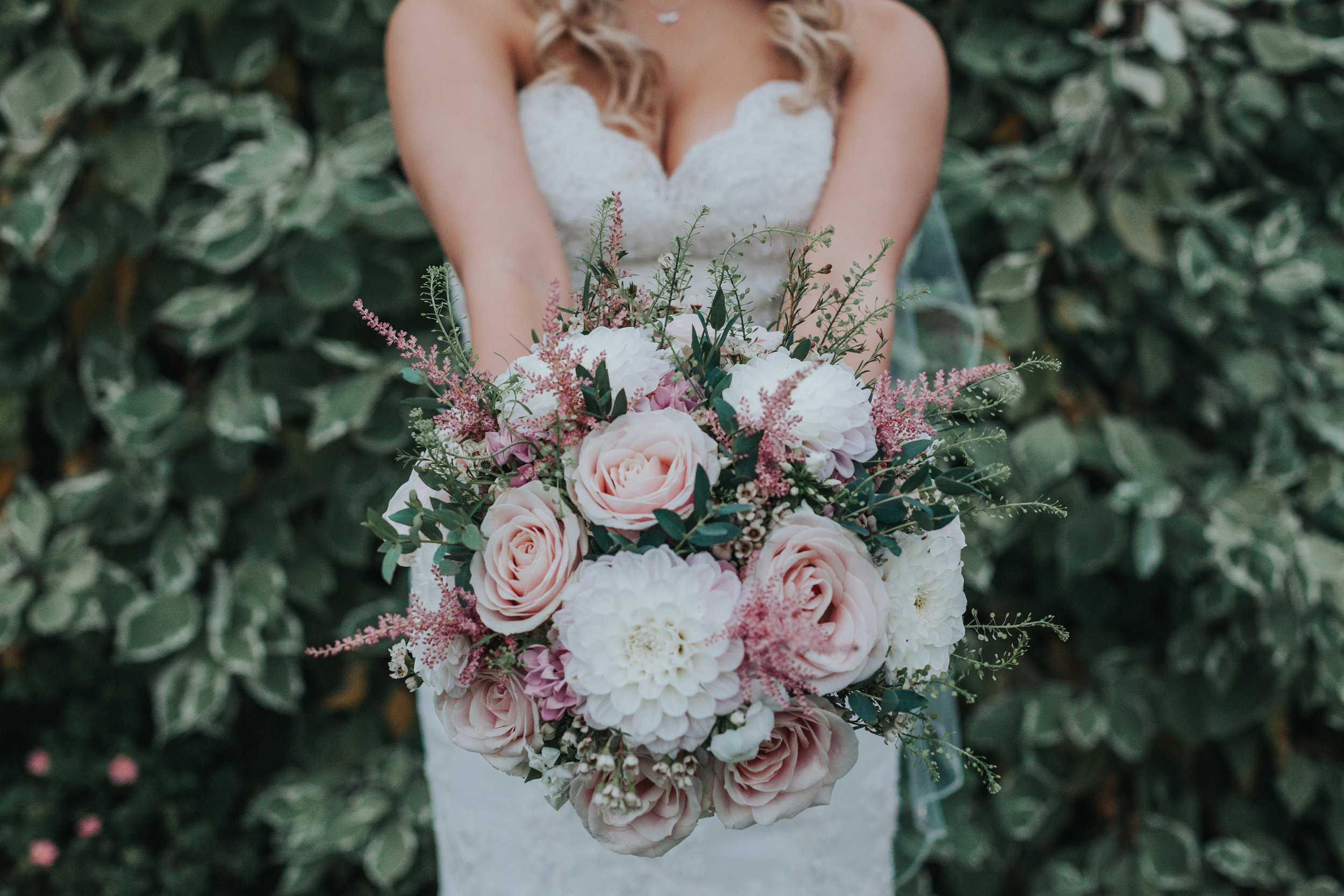 Bride poses with flowers.