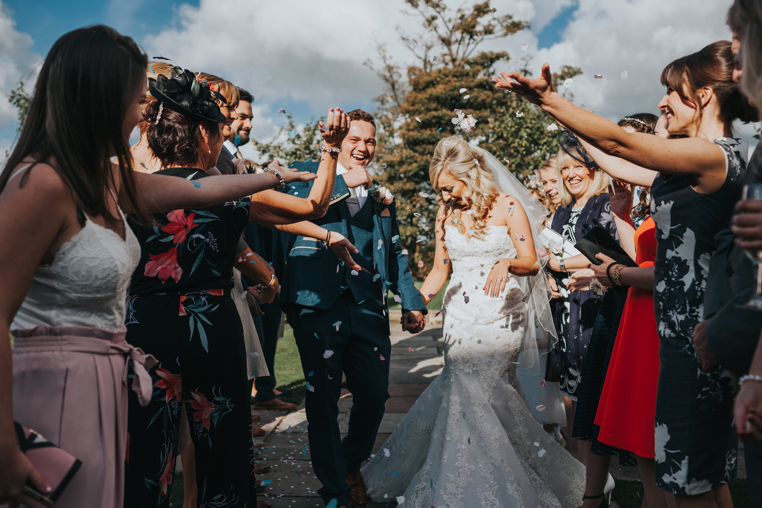 Bride and groom laugh as they are attacked with confetti.