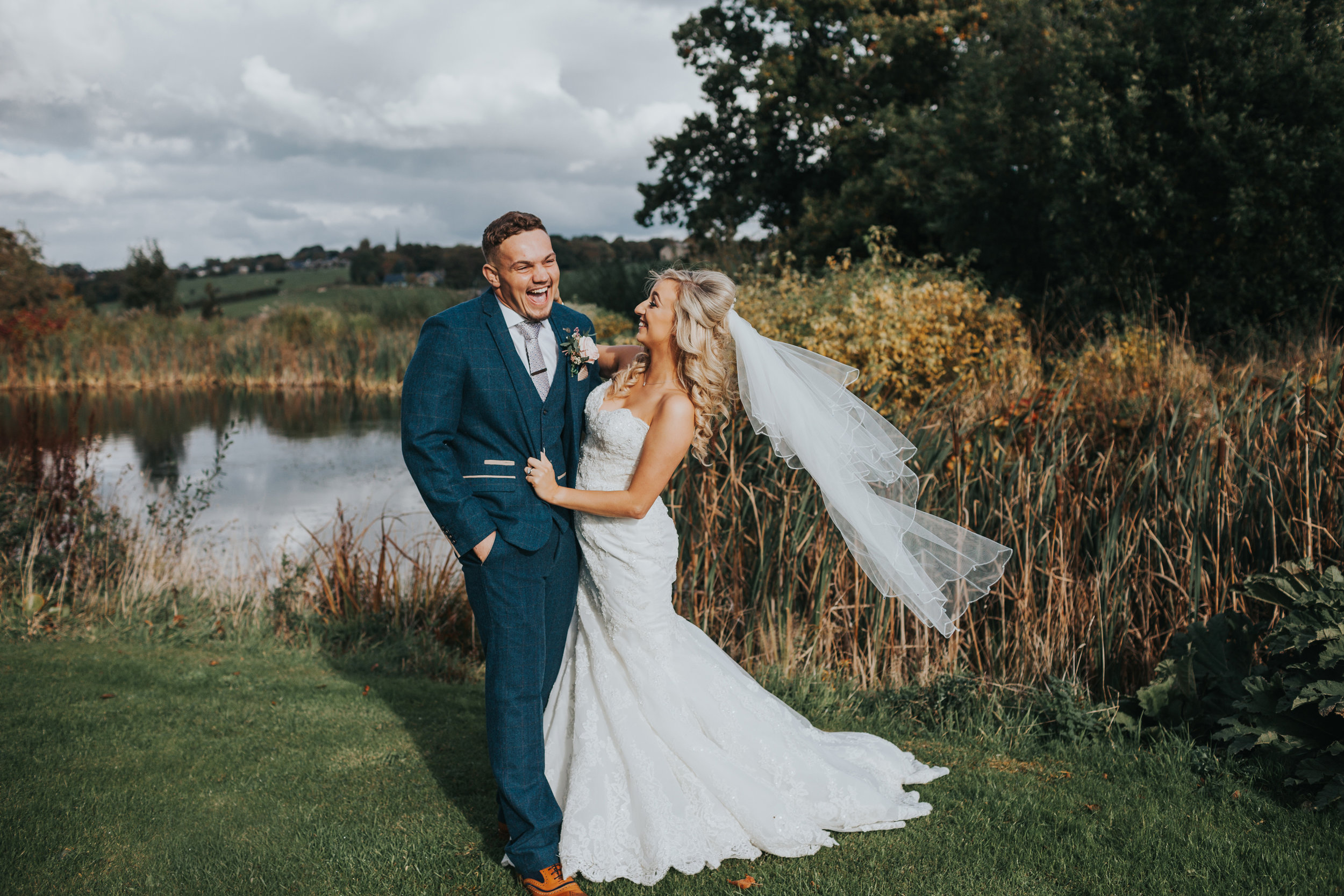 Bride and groom laugh together in front of pond.