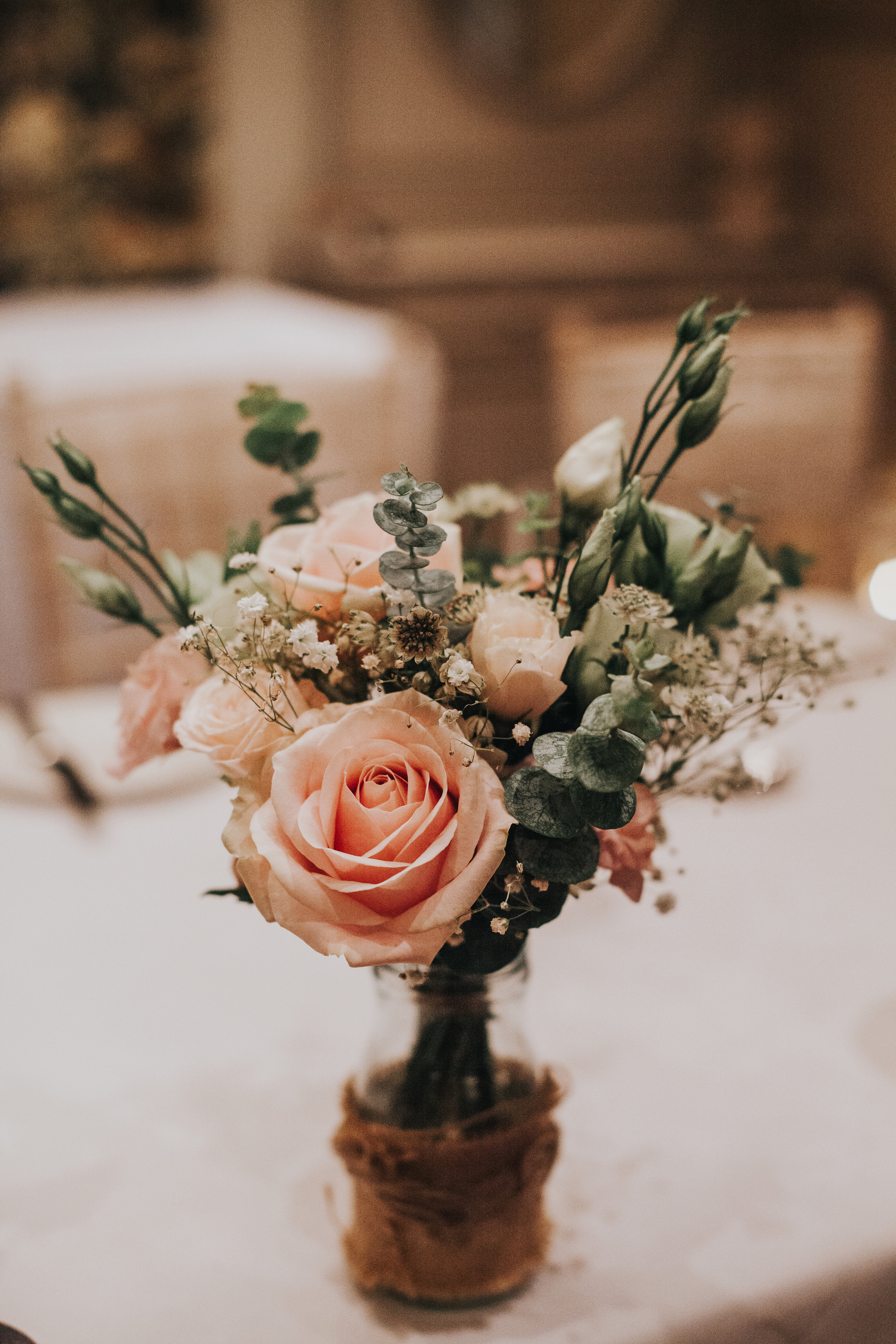 Pink roses and greenery in a jar as a table decoration.