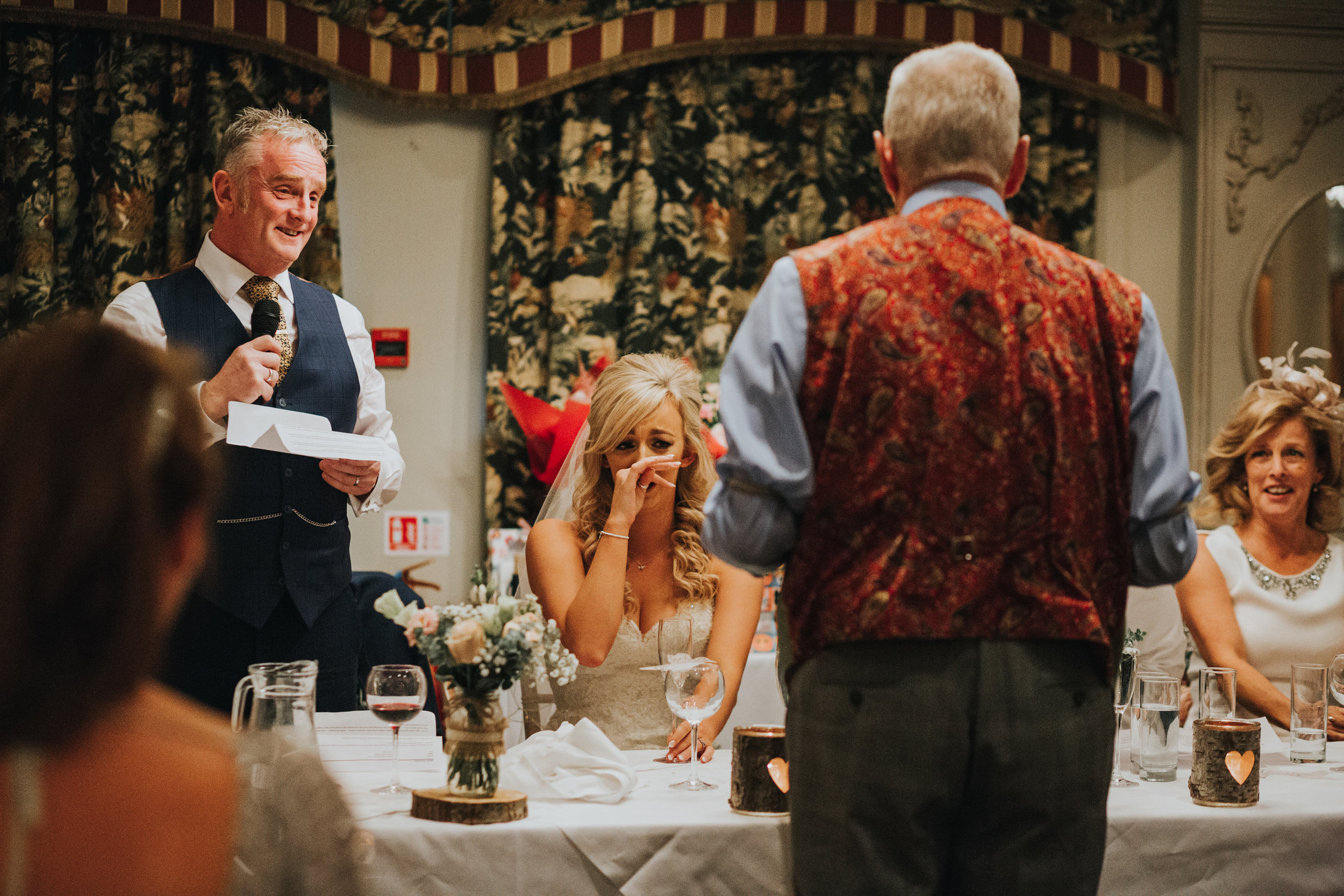 Brides uncle approaches table and bride holds hand over her mouth laughing and looking scared.