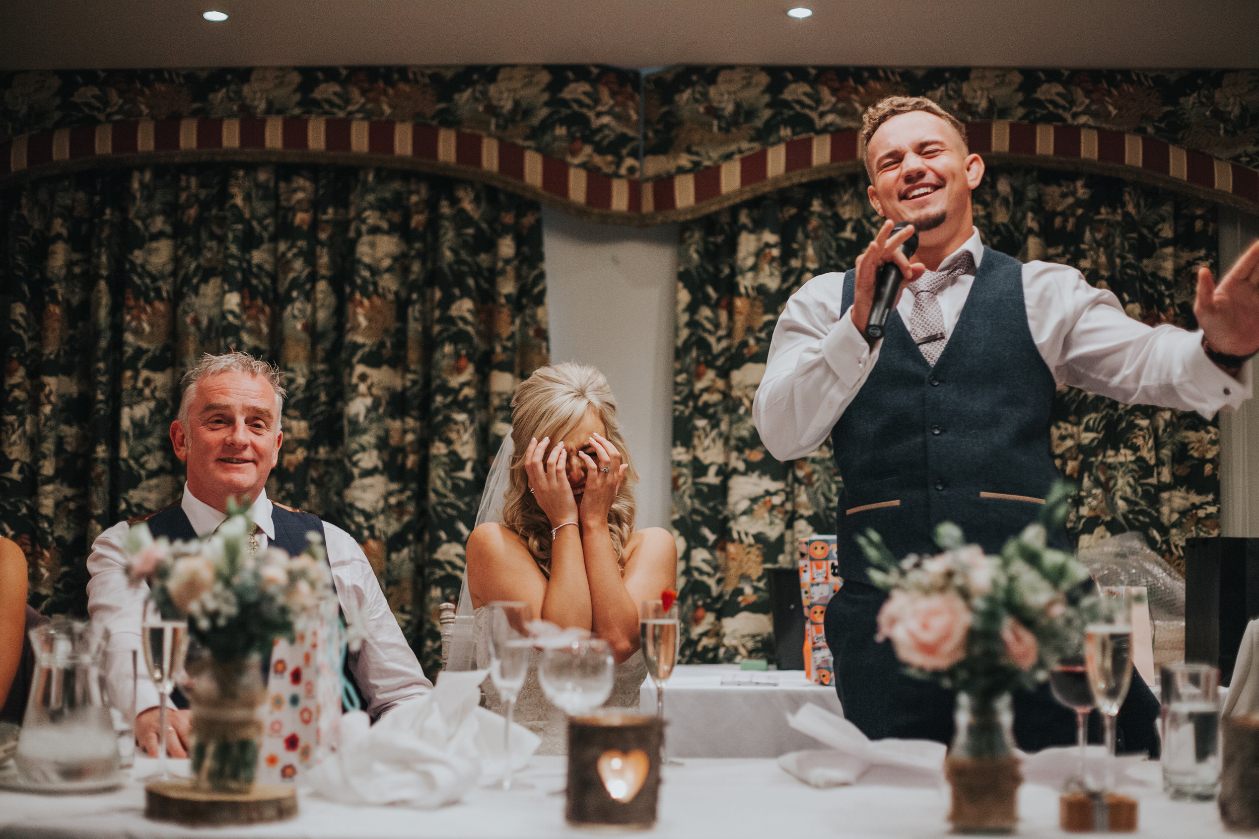 Bride holds hands over her face as her husband makes his speech.
