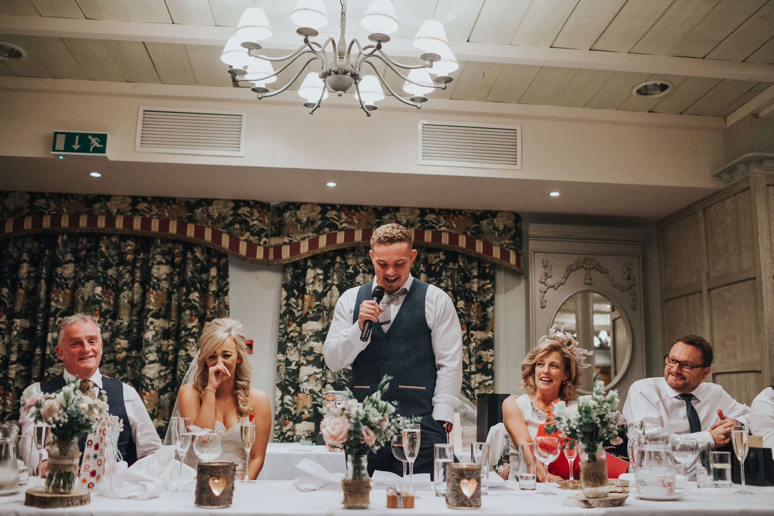 Head table laughs as the groom makes his speech.