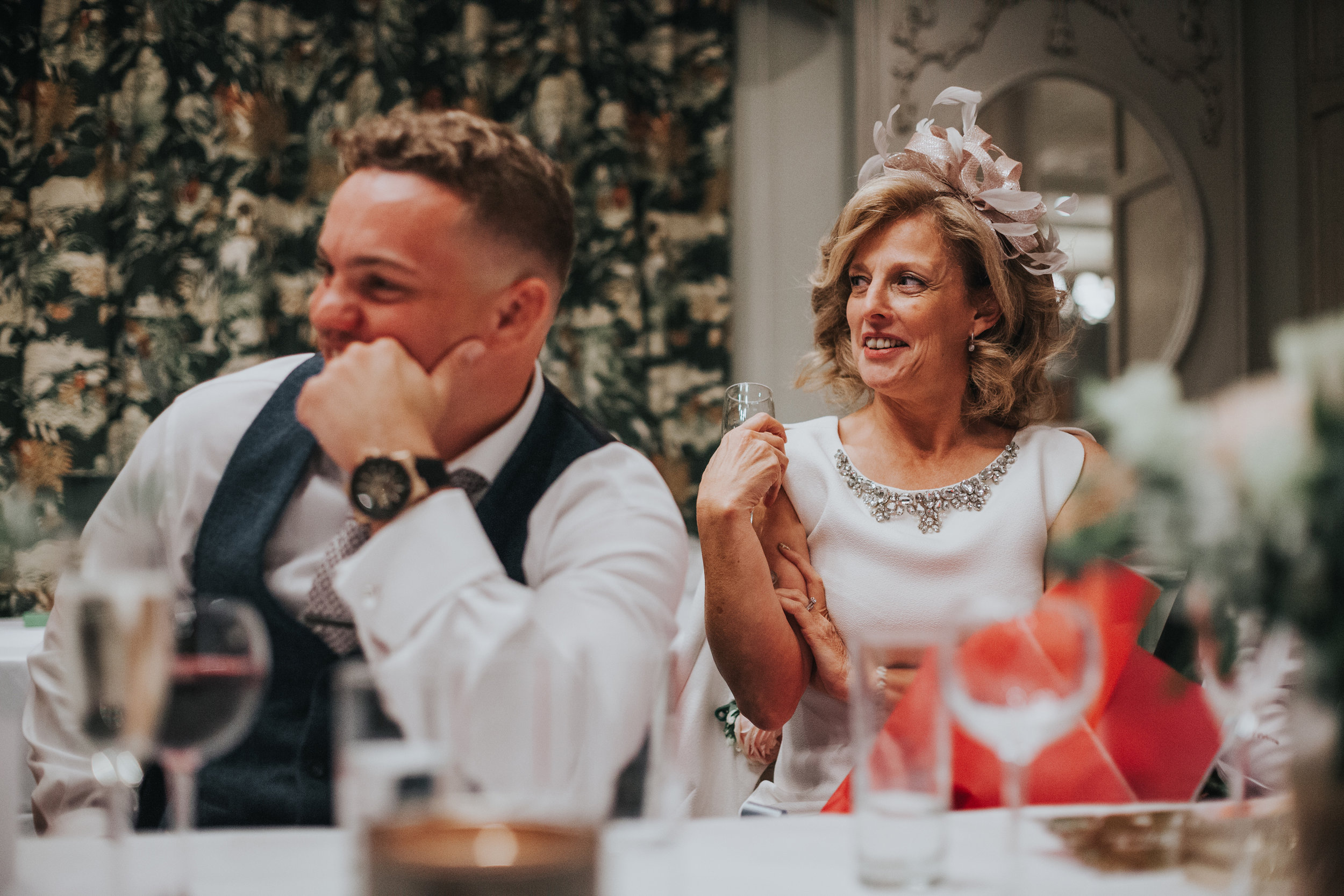 Mother of the bride smiles during best mans speech.