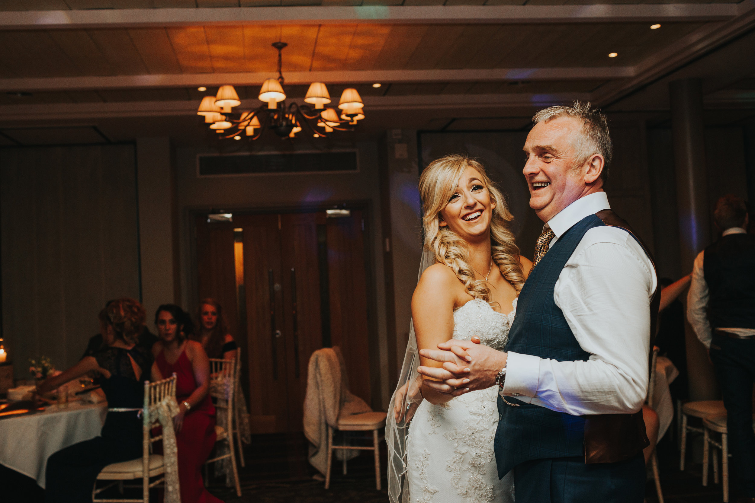 Bride dances with her Dad smiling.
