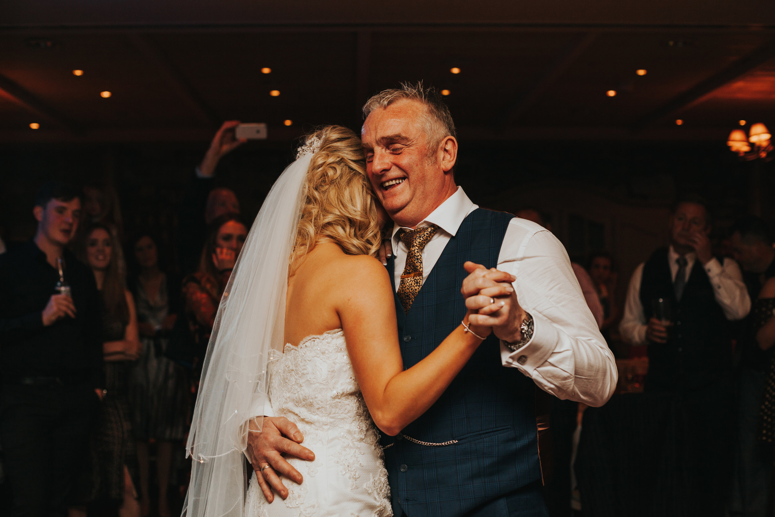 Dad laughing as he dances with his daughter.
