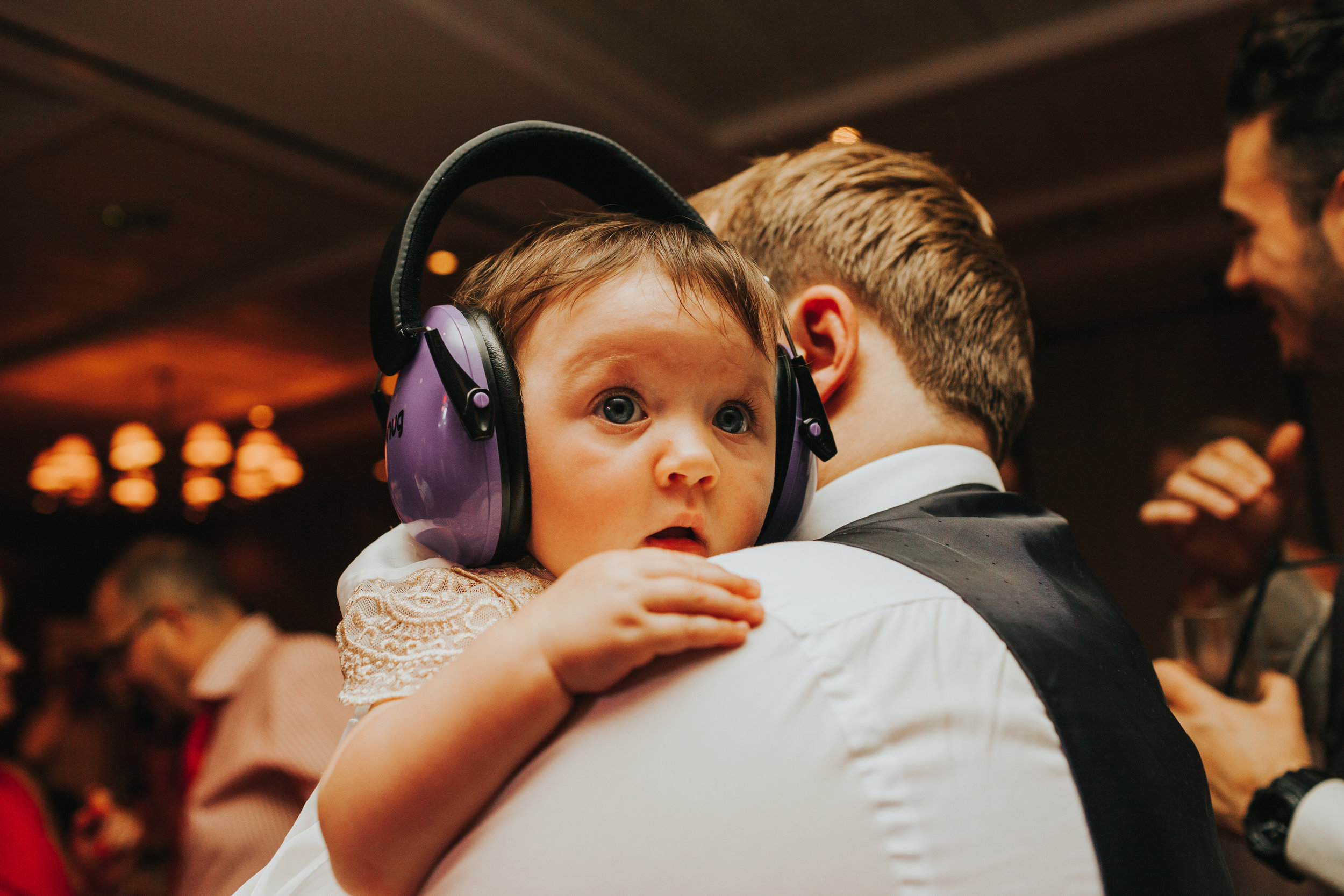 Cute baby with noise cancelling headphones on looking tired.