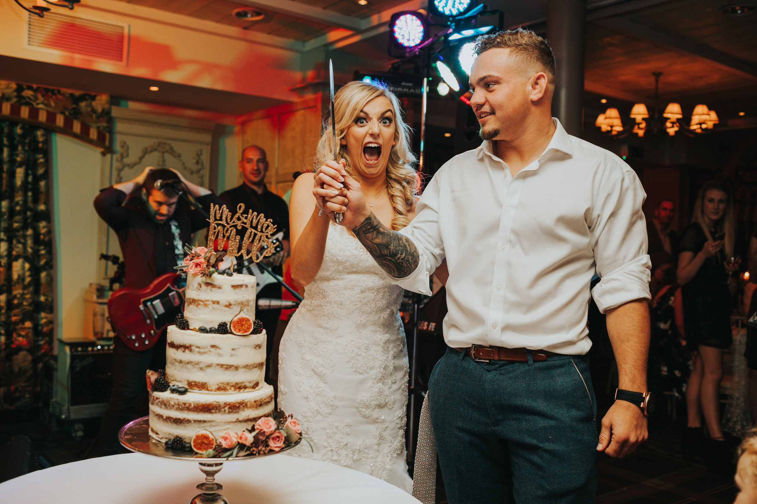Bride pulls silly face as they cut the cake.