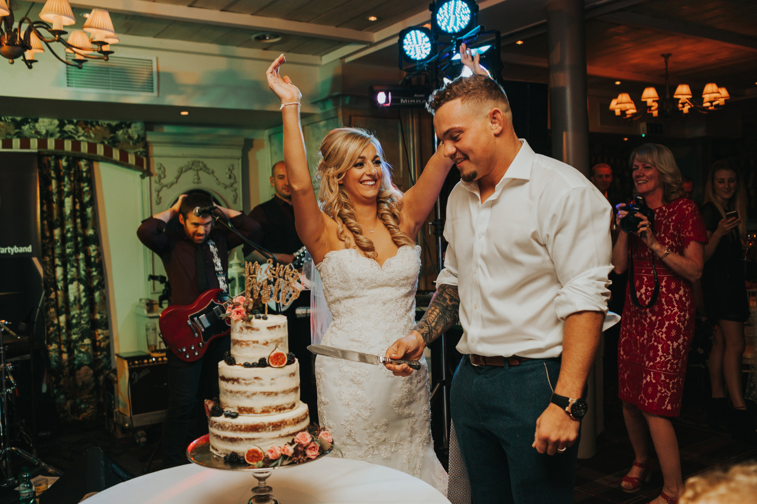 Bride celebrates as they cut the cake.