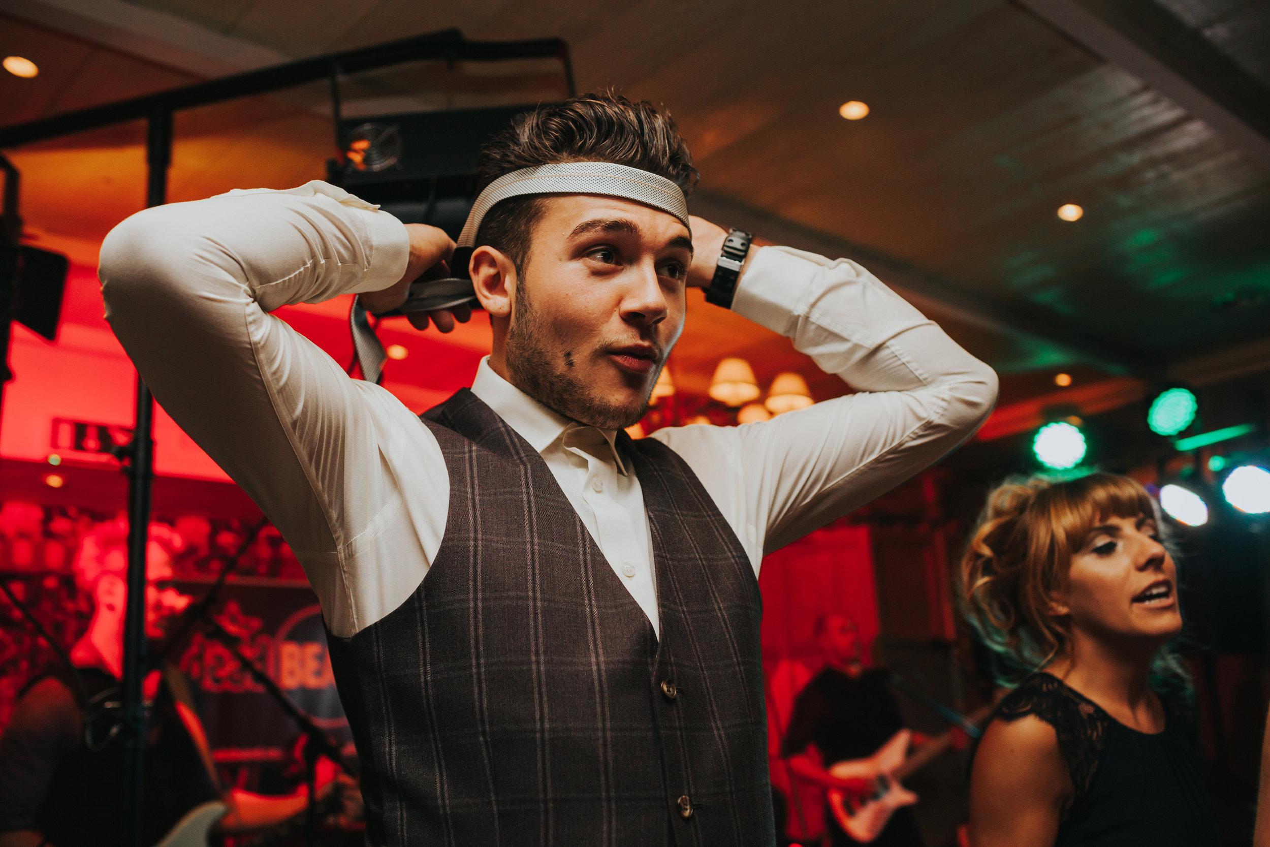Guest ties his tie around his head.