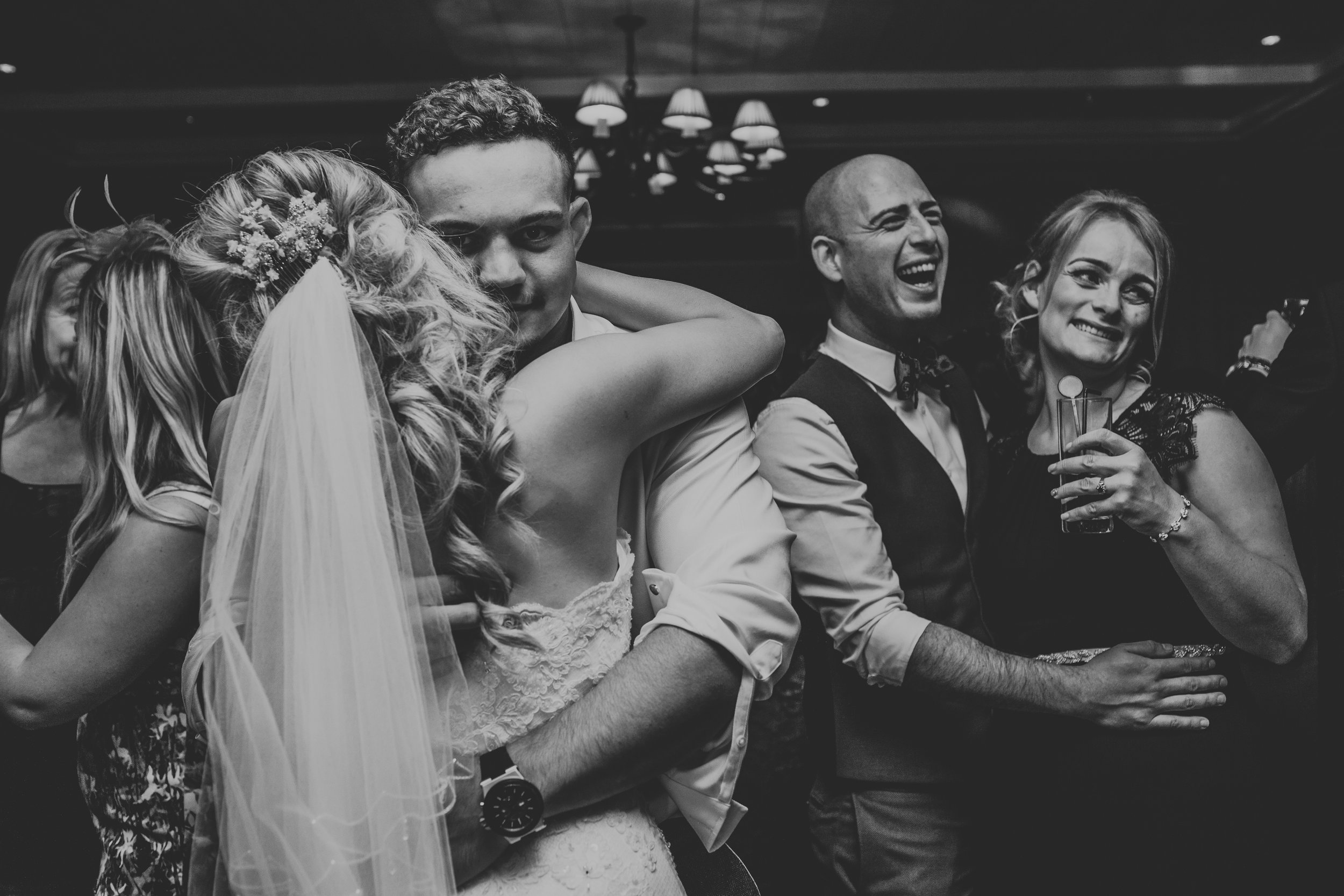 Bride and groom embrace on dance floor as guests laugh in the back ground.