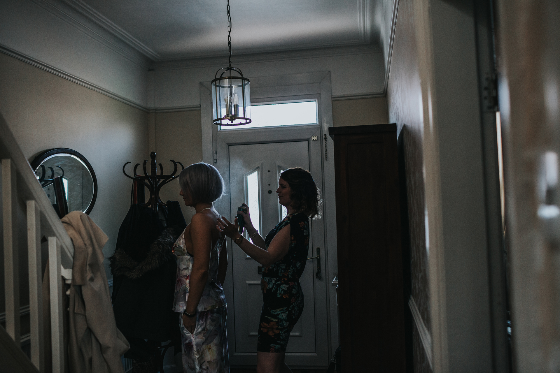 Bridesmaids do each others hair in hallway of the brides house, Manchester.