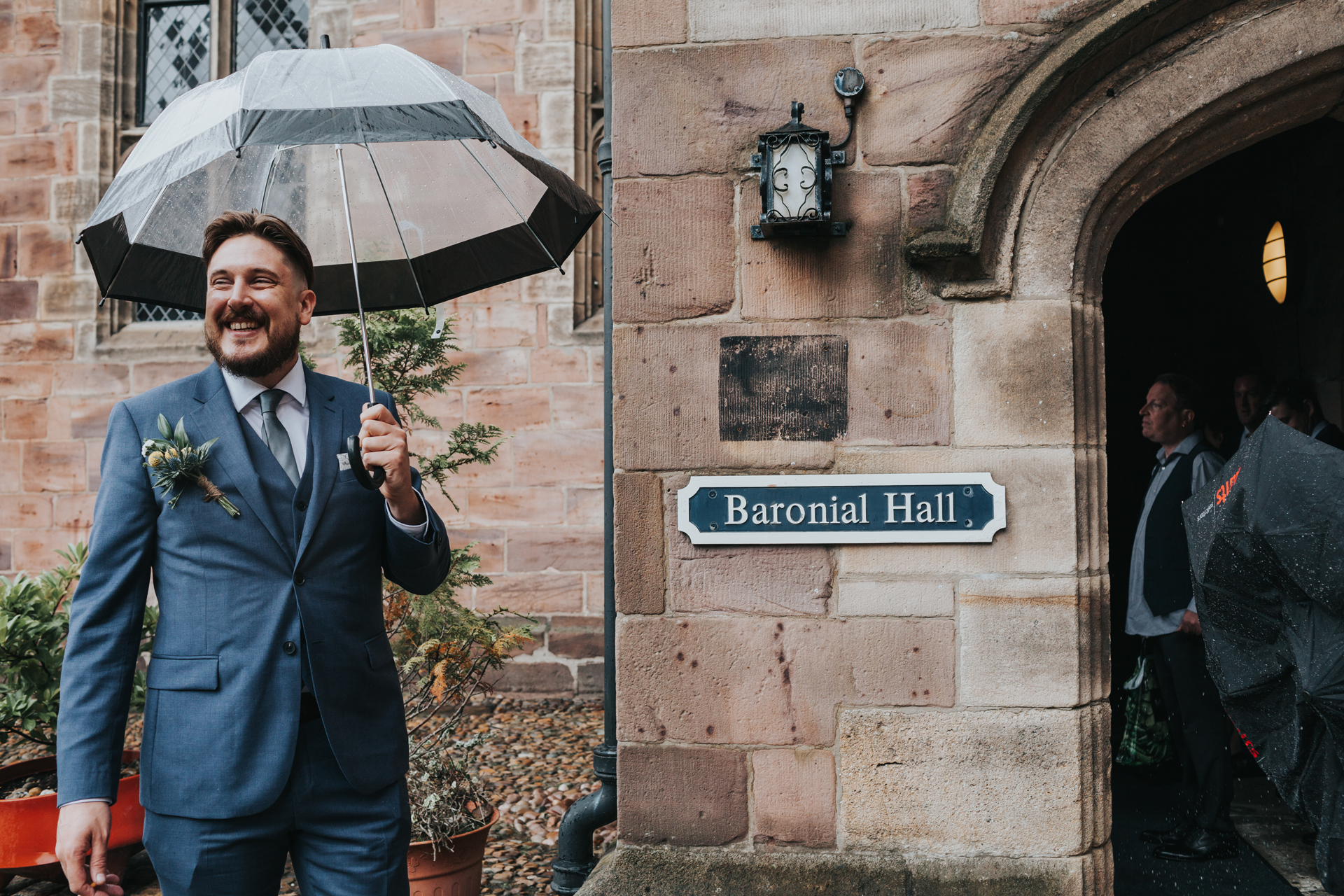 Groom welcomes wedding guests under umbrella outside Chetham Library.