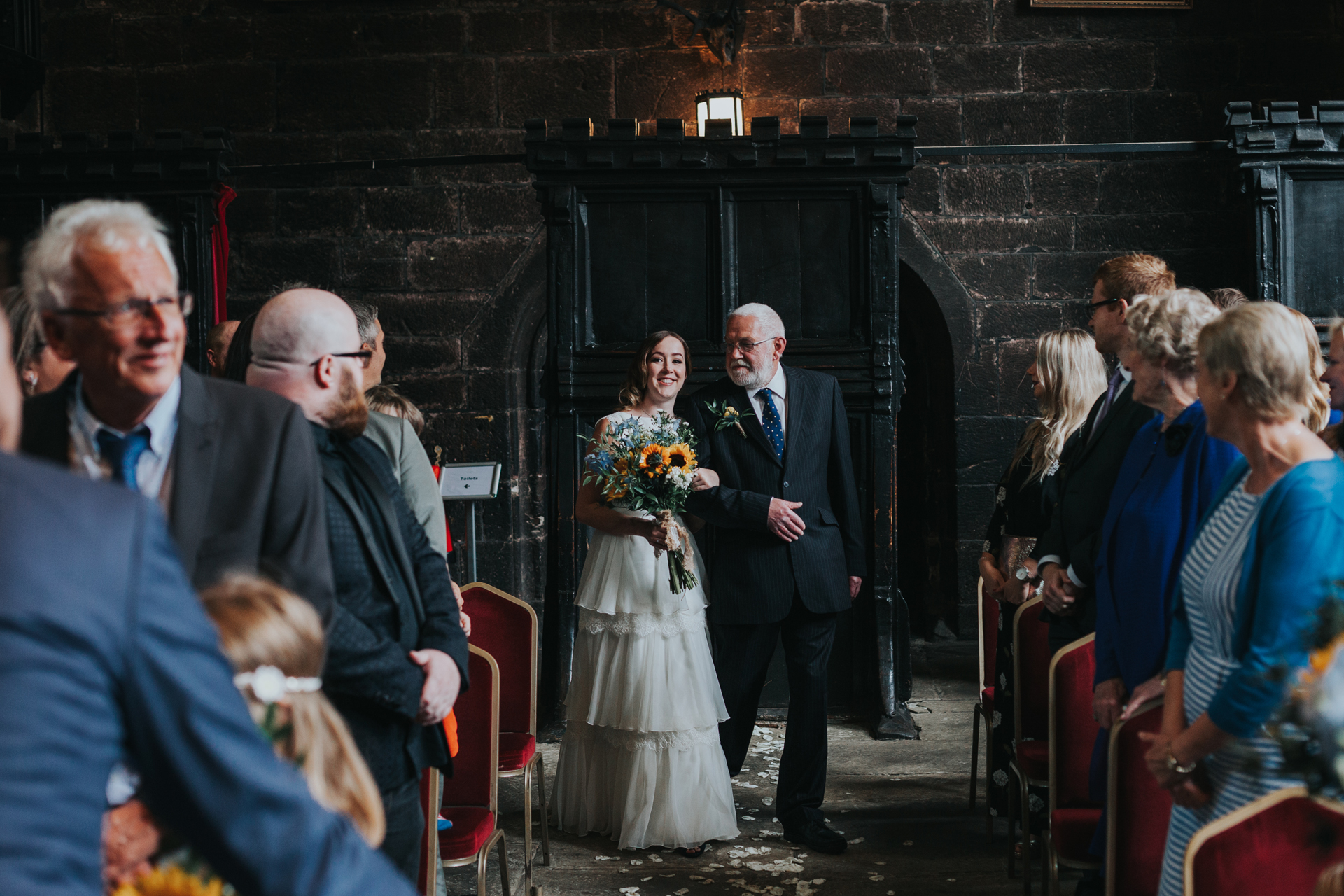 Bride is walked down the aisle by her father at Chetham's Library.