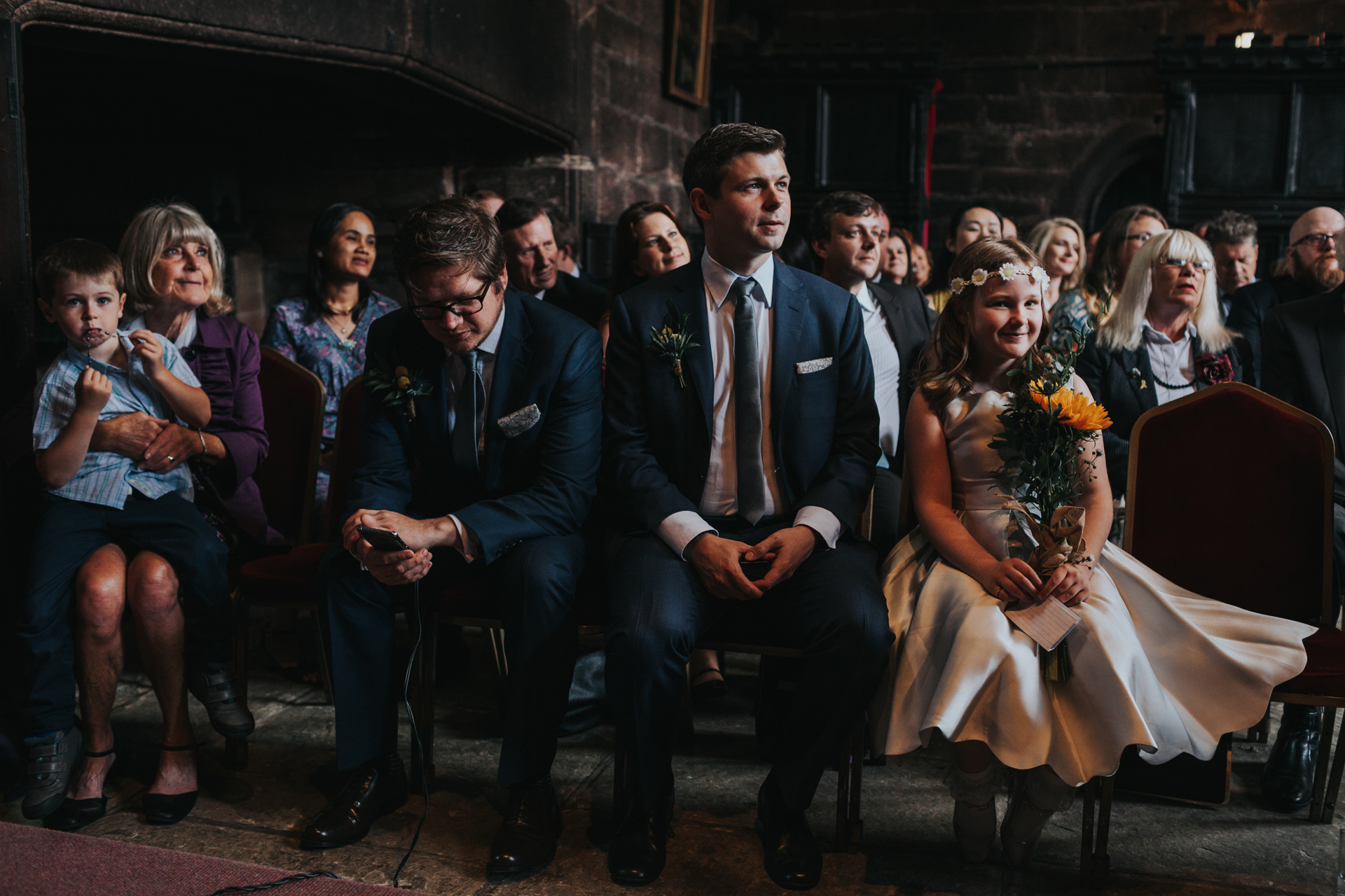 Bridesmaid sits with groomsmen looking very excited!