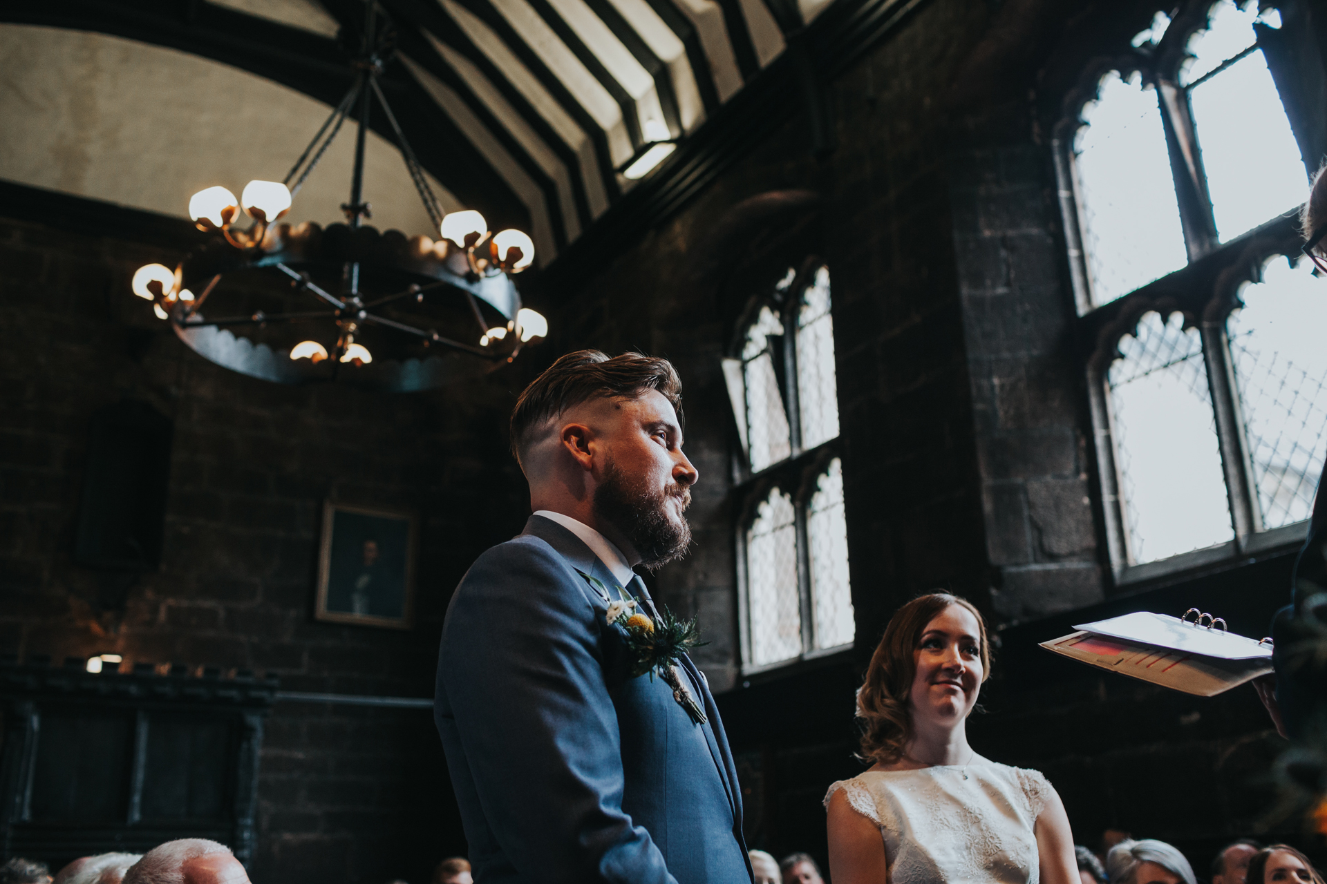 Groom stands next to bride at Chetham's Library Manchester.