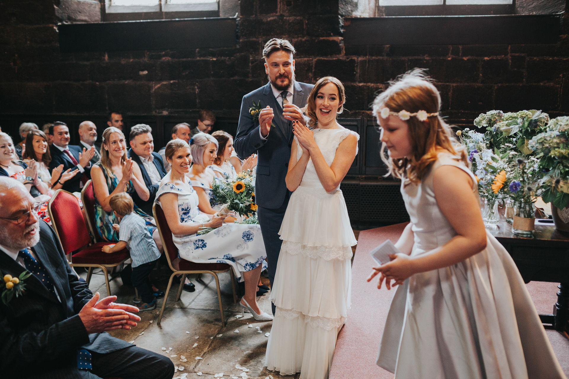 Bridesmaid jumps off the stage as the Bride and Groom clap.