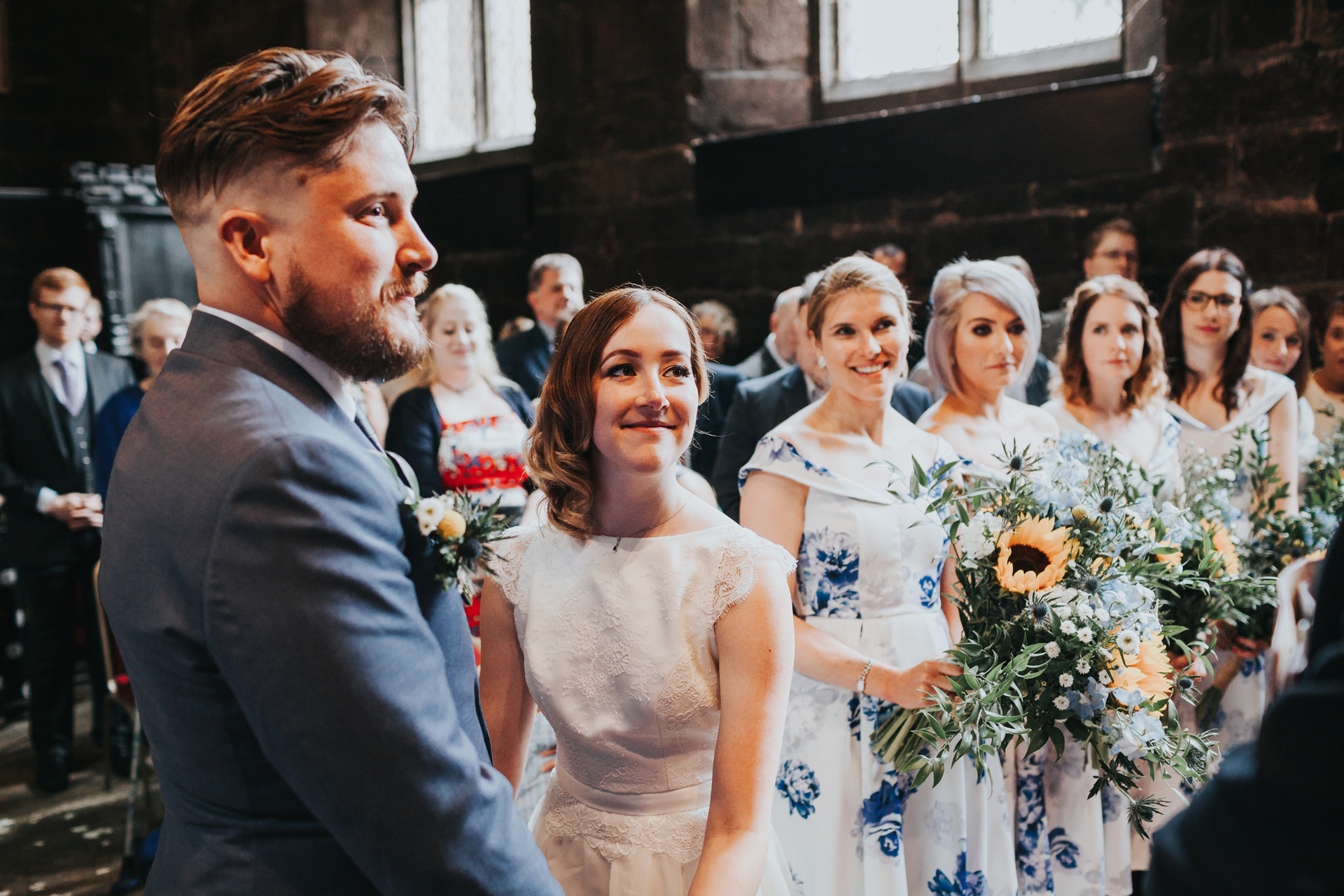 Bride and Groom stand together with a row of Bridesmaids behind them at Chatham Library Manchester.