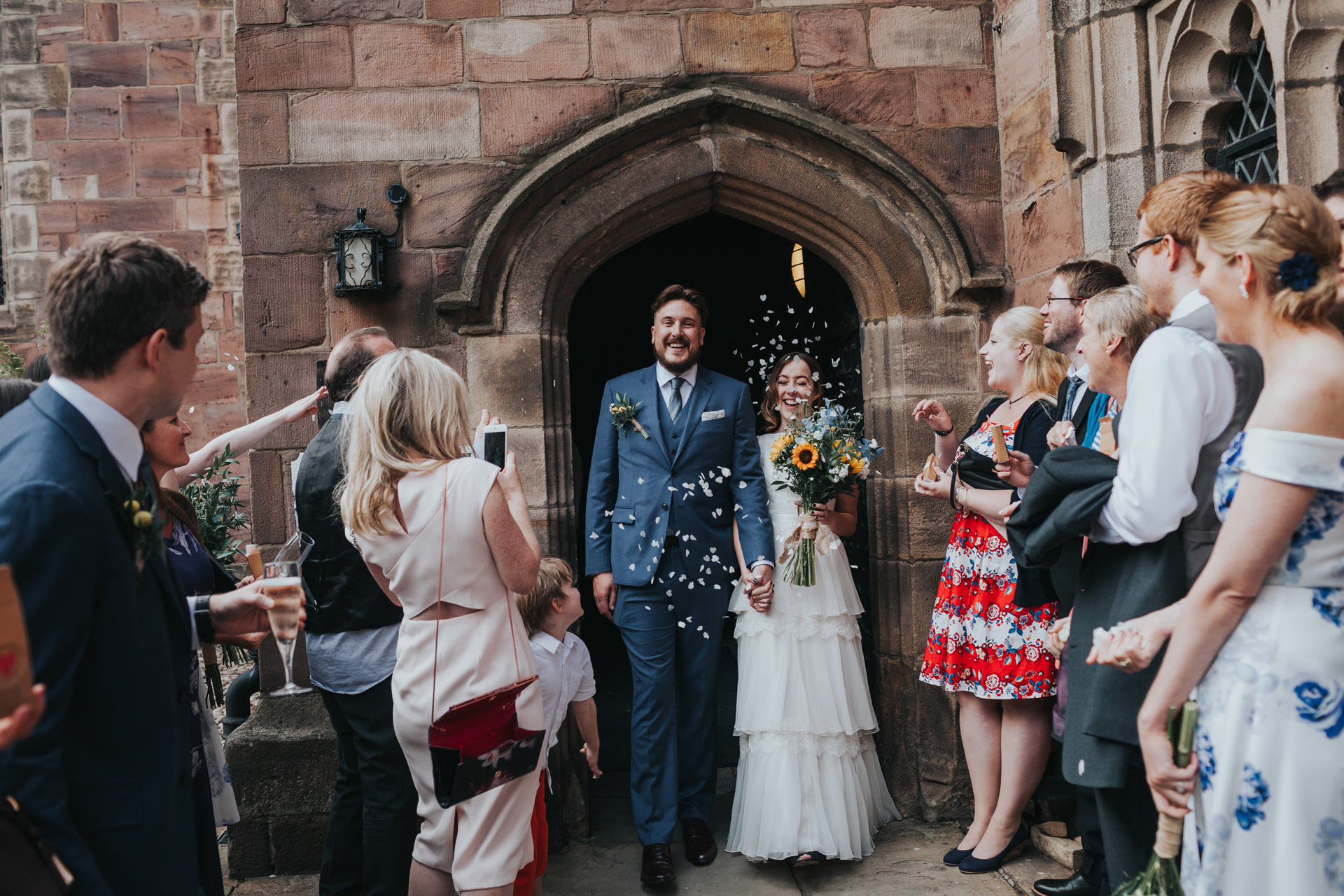 Bride and Groom exit Chetham Library to be greeting by wedding guests throwing confetti.