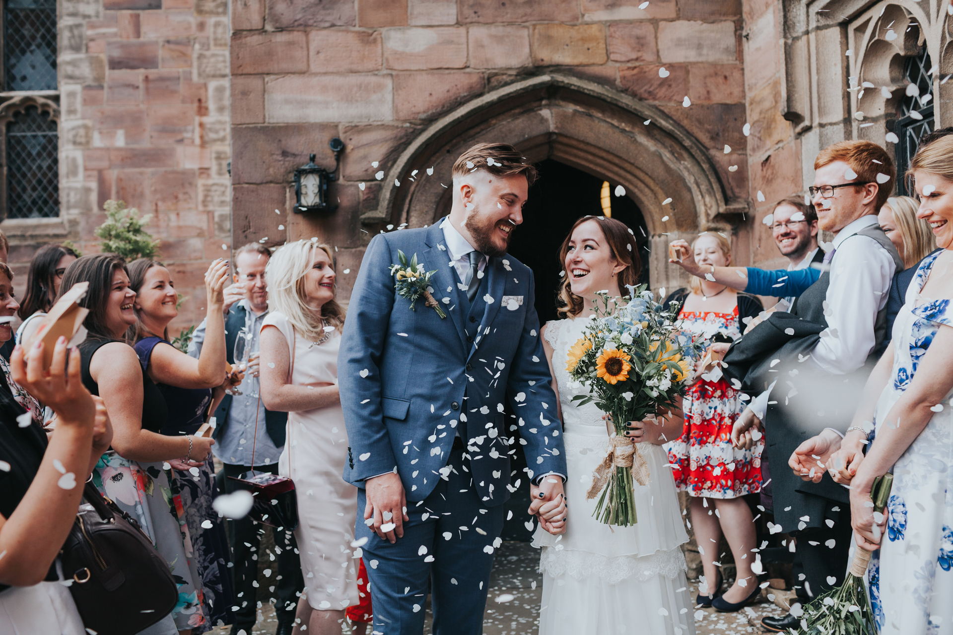 Bride and Groom look at one and other outside Chetham's Library.