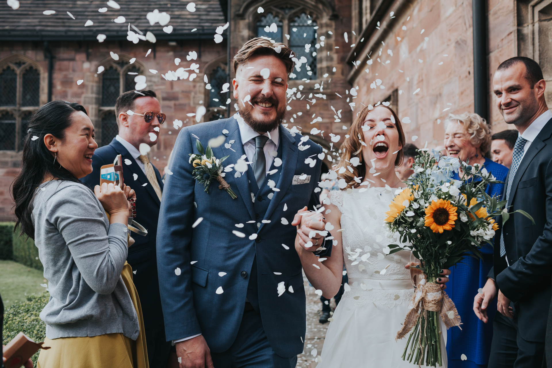 Bride and Groom have confetti thrown at them by their wedding guests outside Chetham Library and look very excited about it!