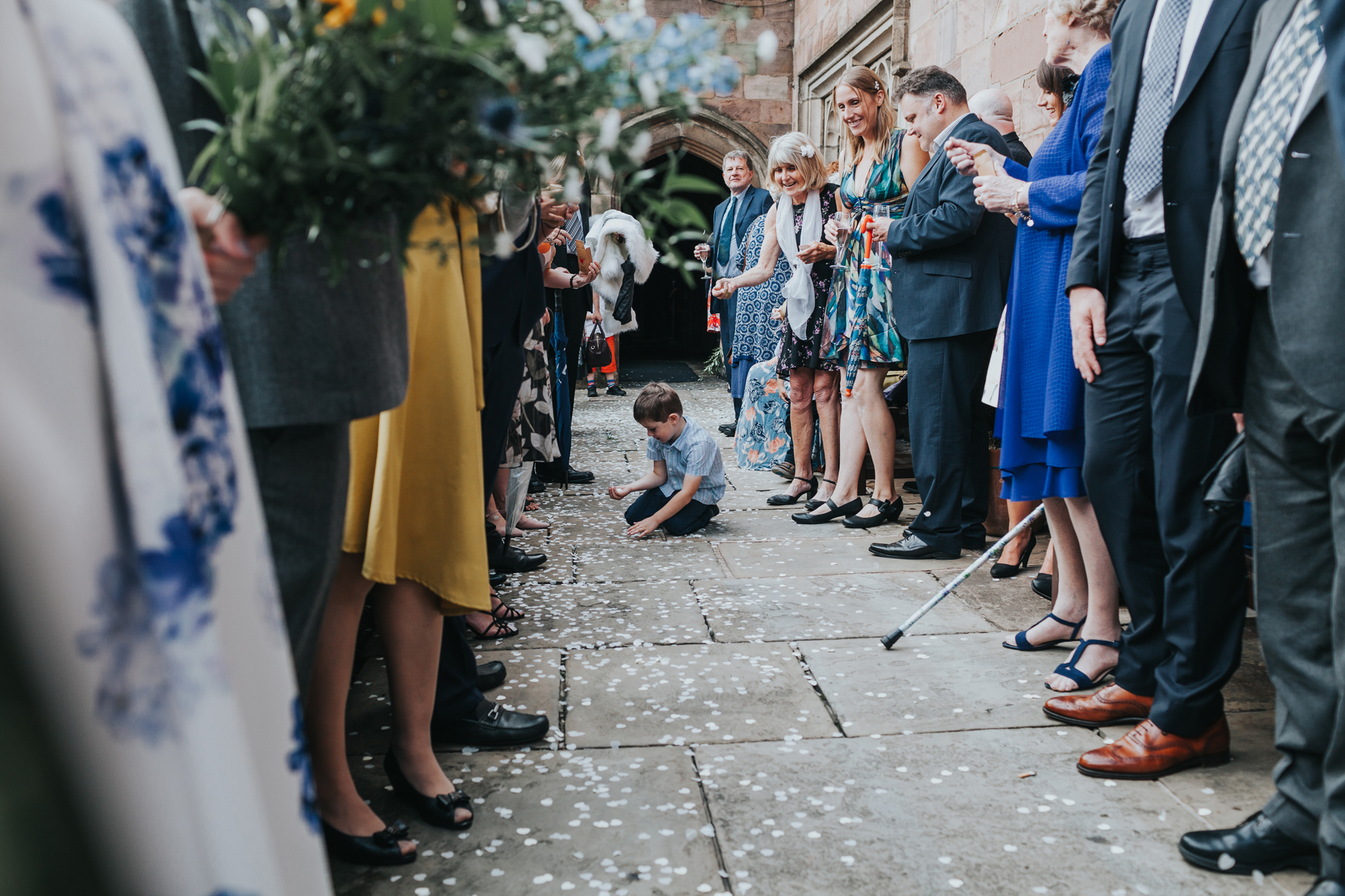 Little boy picks confetti up off the floor.