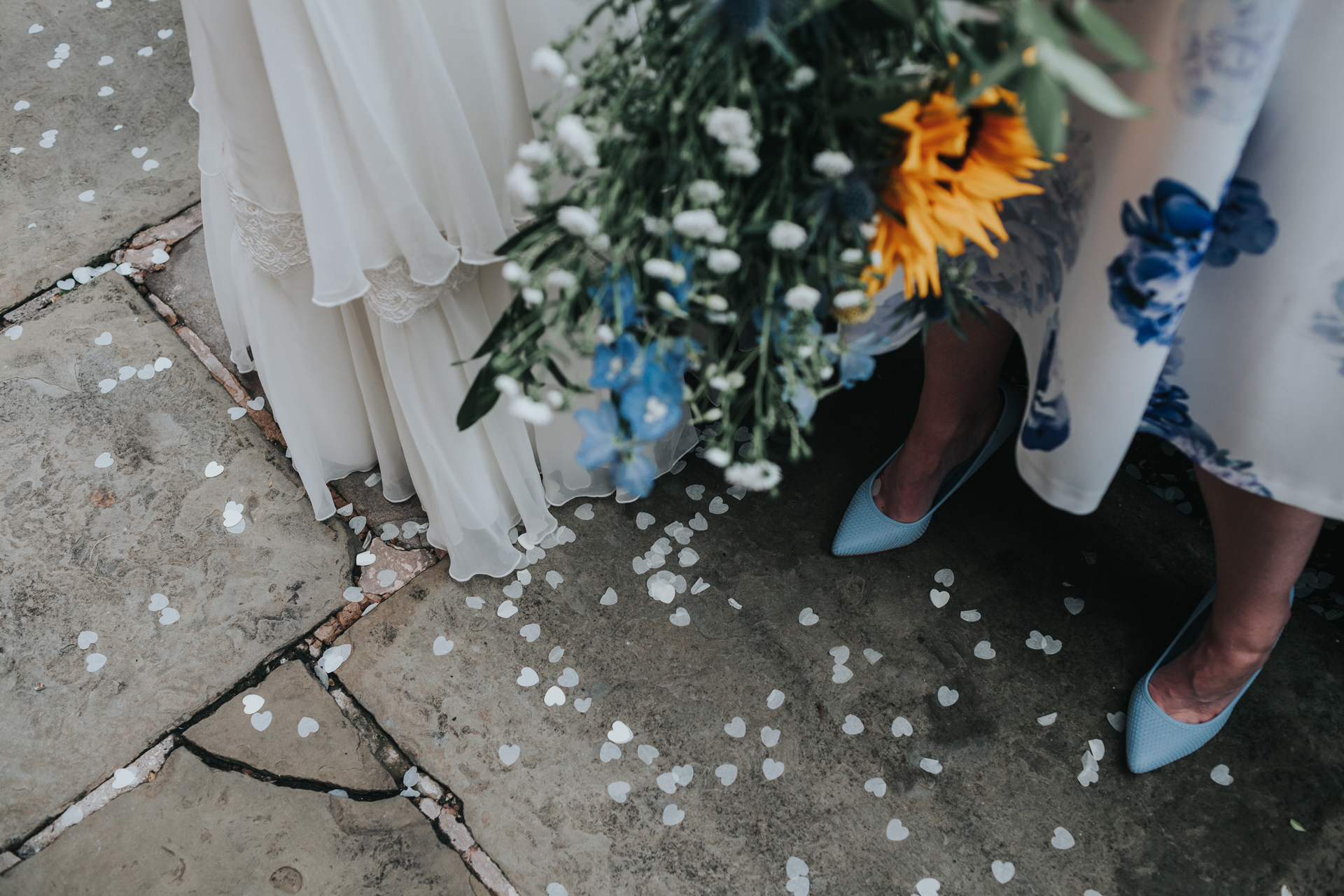Brides dress, flowers, shoes and confetti.