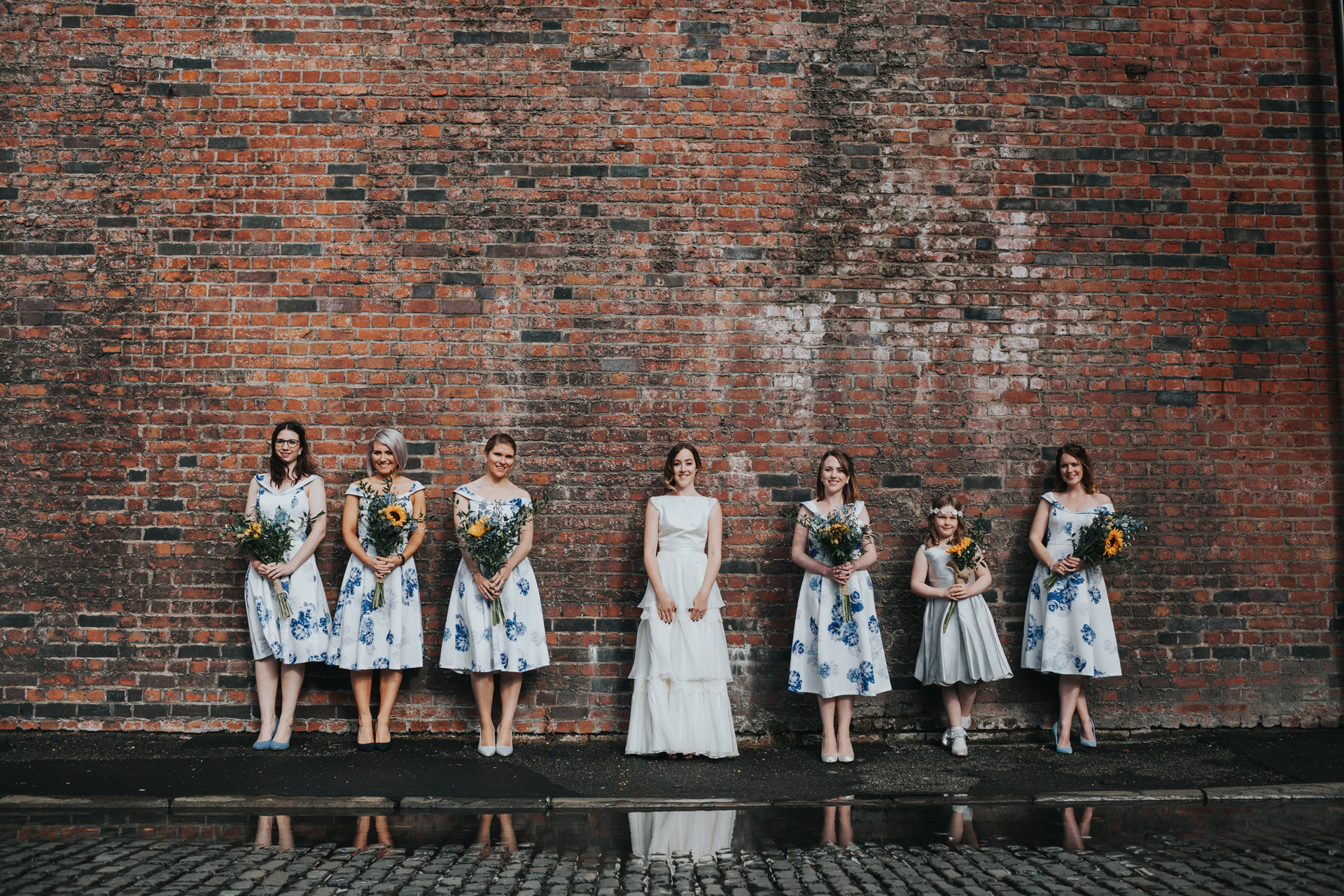 Bride and Bridesmaids stand in front of puddle outside Lock 91.