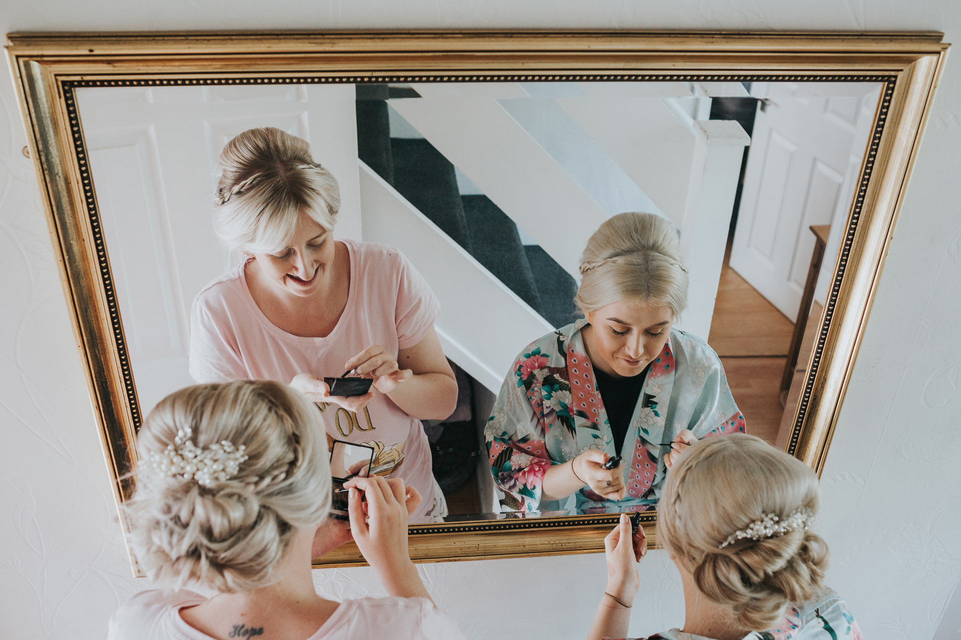 Bridesmaids putting make up on in the mirror at home in Manchester