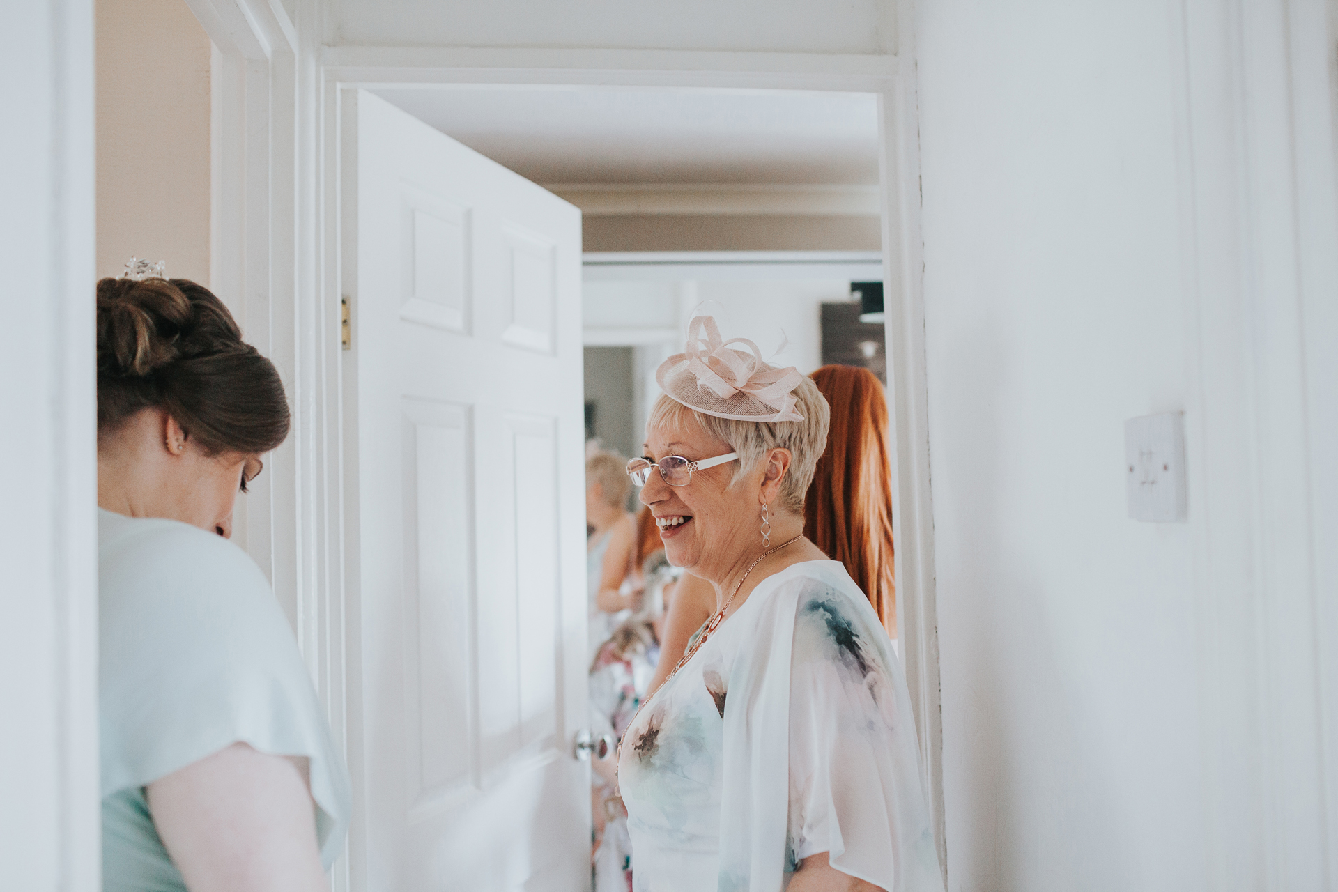 Mother of the bride looks excited waiting for her daughter in the hallway.