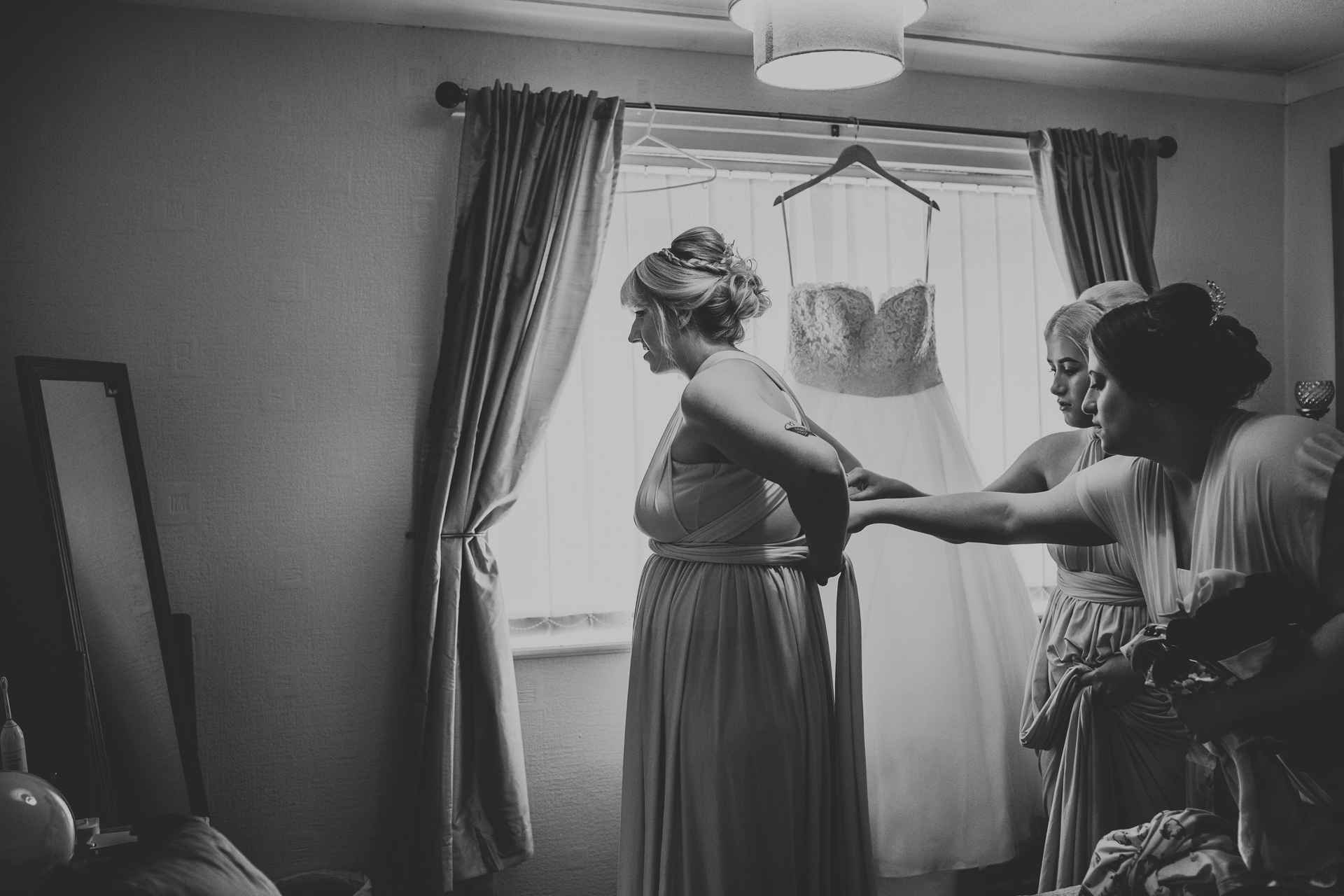 Bridesmaids help to dress another in front of a window, the wedding dress hangs from the curtain rail above the window.