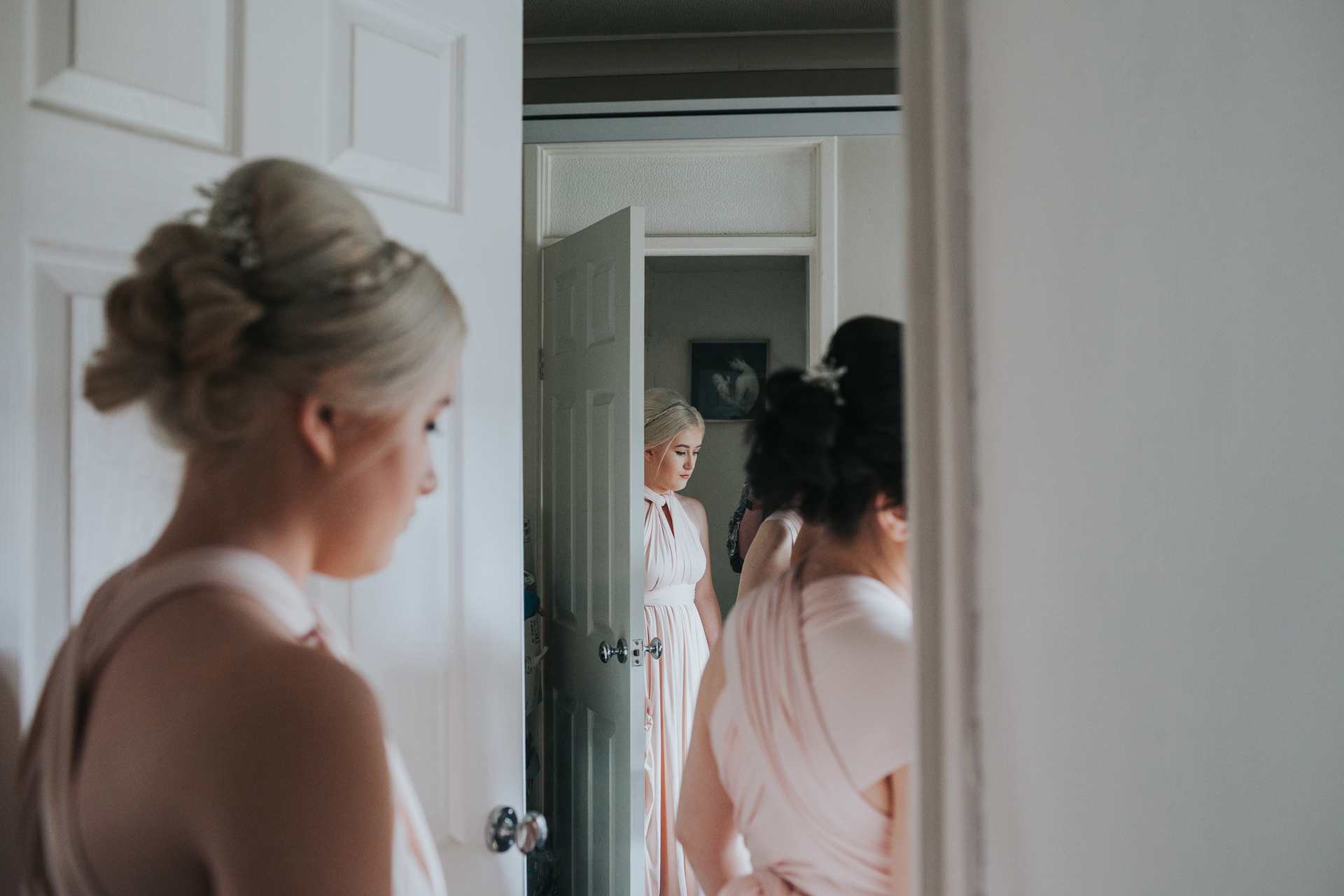 Bridesmaid waits outside the door for the bride, we see her in the foreground and back ground of the photograph as she is reflected in the mirror beyond the door.