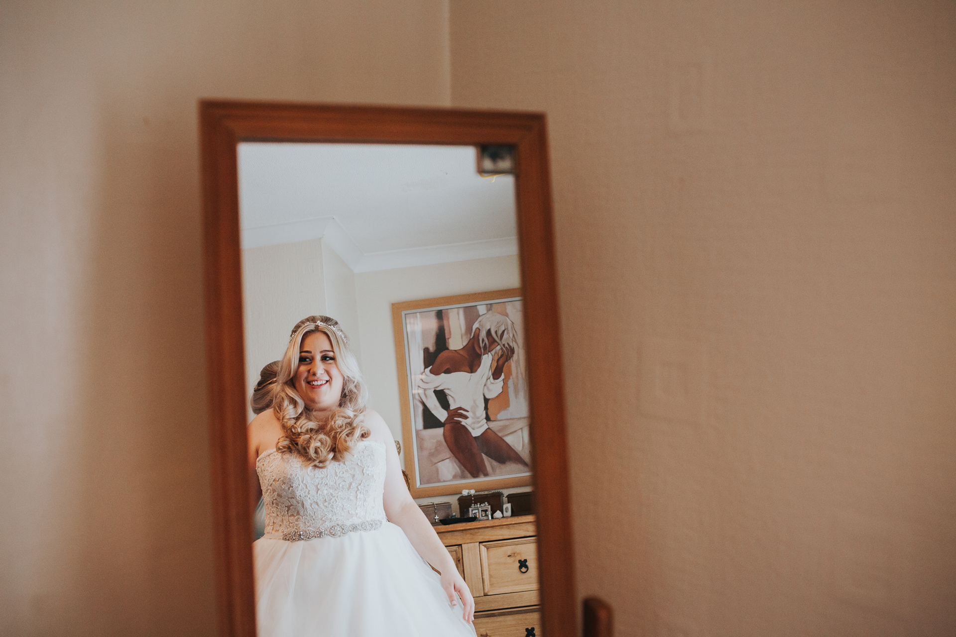 Brides reflection in the mirror as she wears her wedding dress.