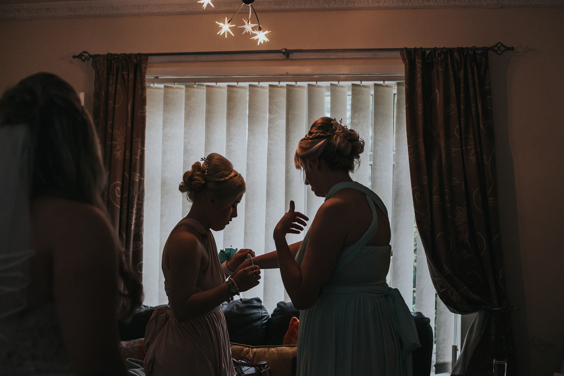 Silhouette of bridesmaids getting ready in front on the window.