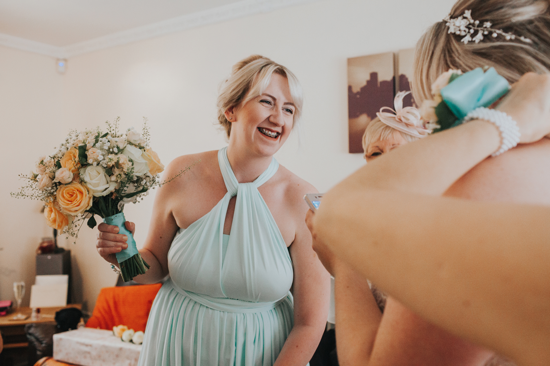 Bridesmaid leans forward laughing holding her flowers.