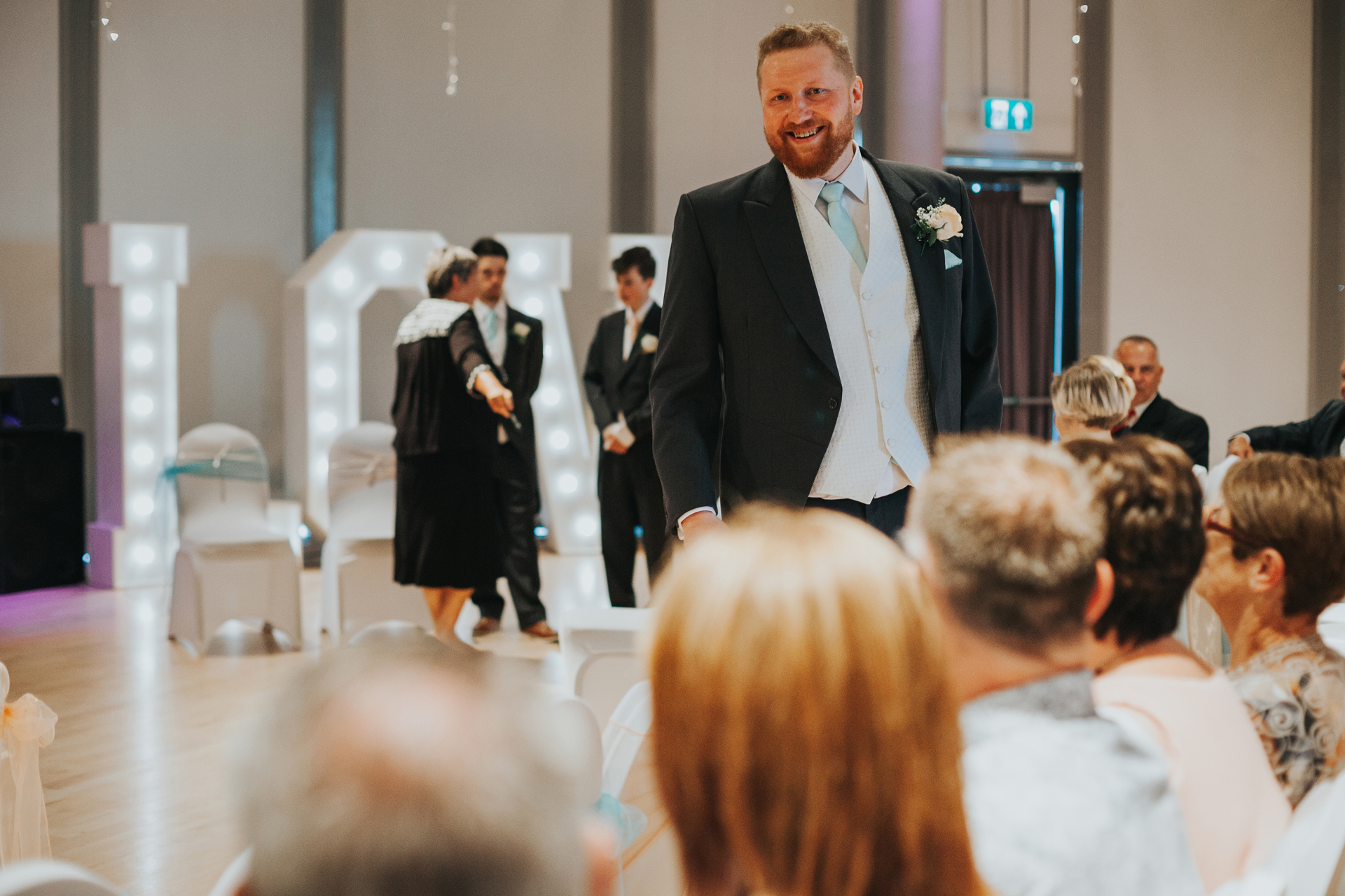 Groom looks on at guests smiling as he waits for his bride.