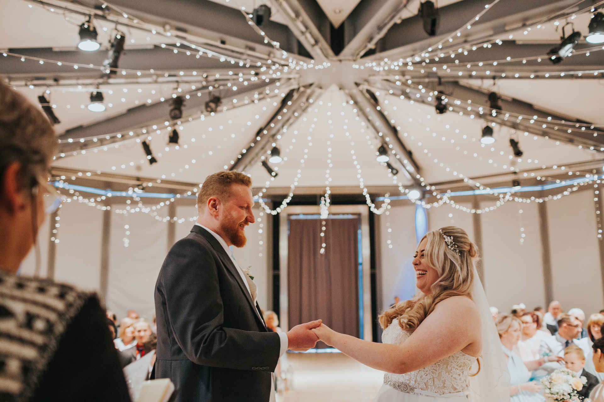 Bride and Groom hold hands with fairy lights twinkling behind them.