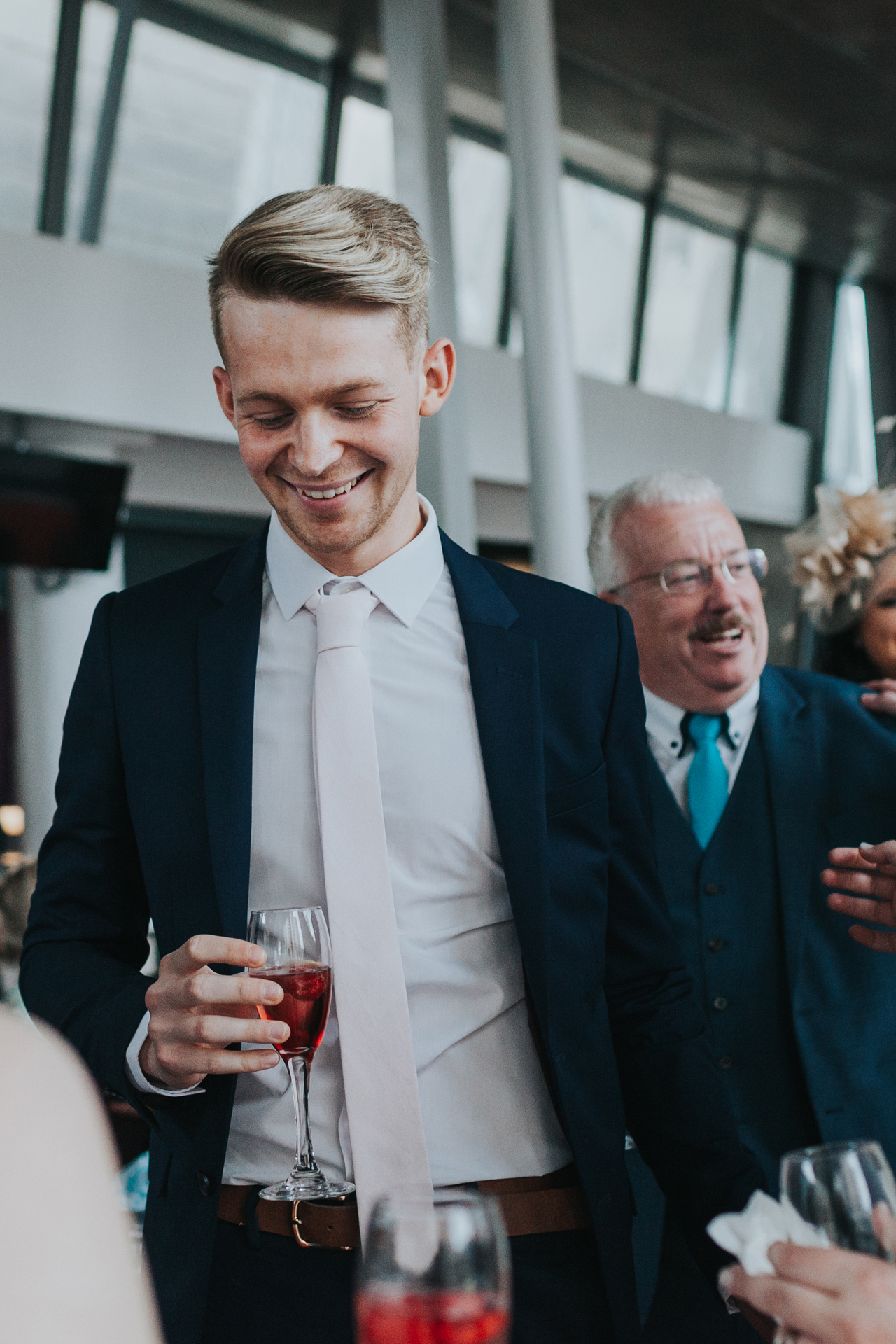 Young wedding guest looks pleased with himself.